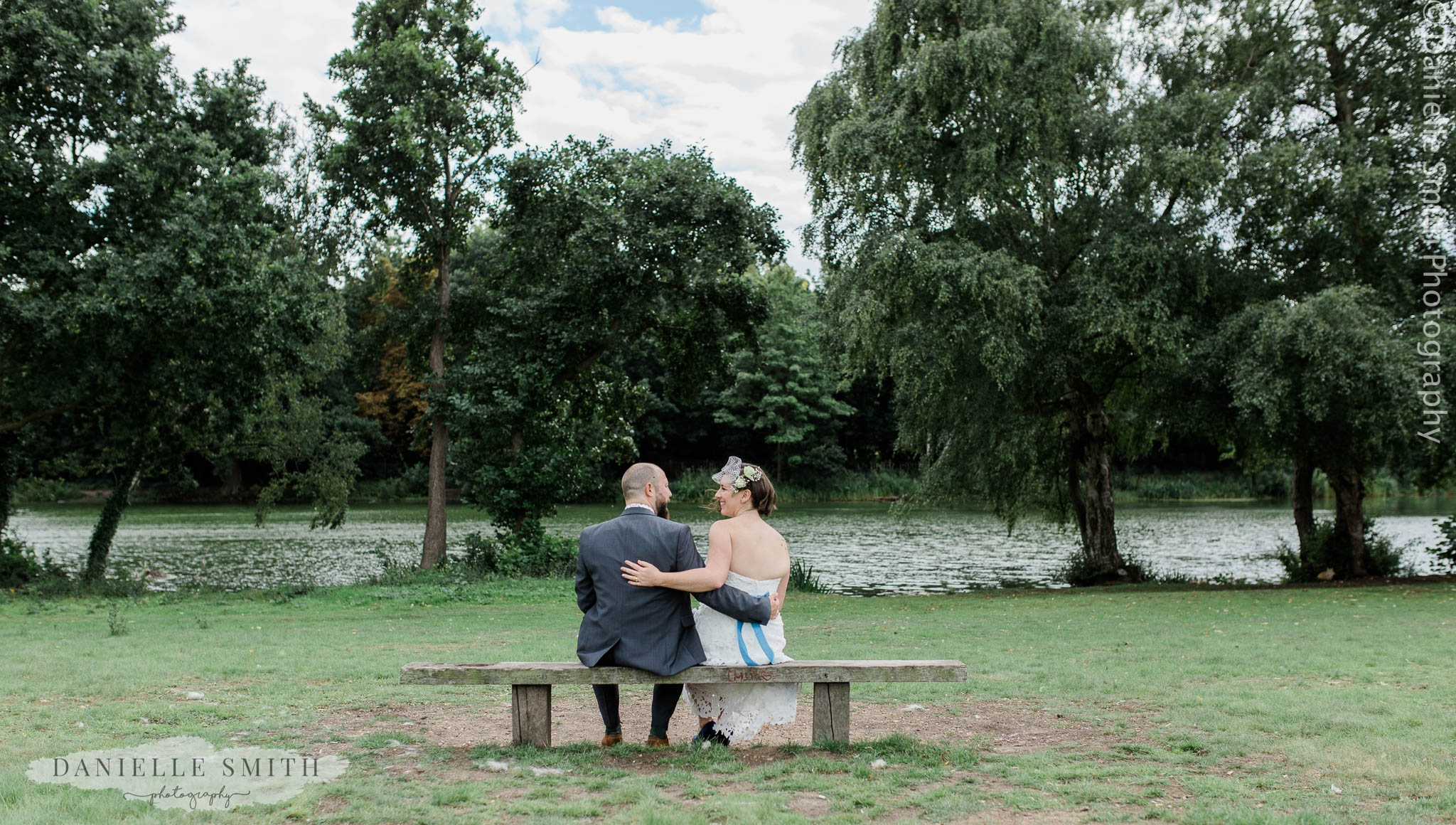 bride and groom sitting on bench in park - east london wedding