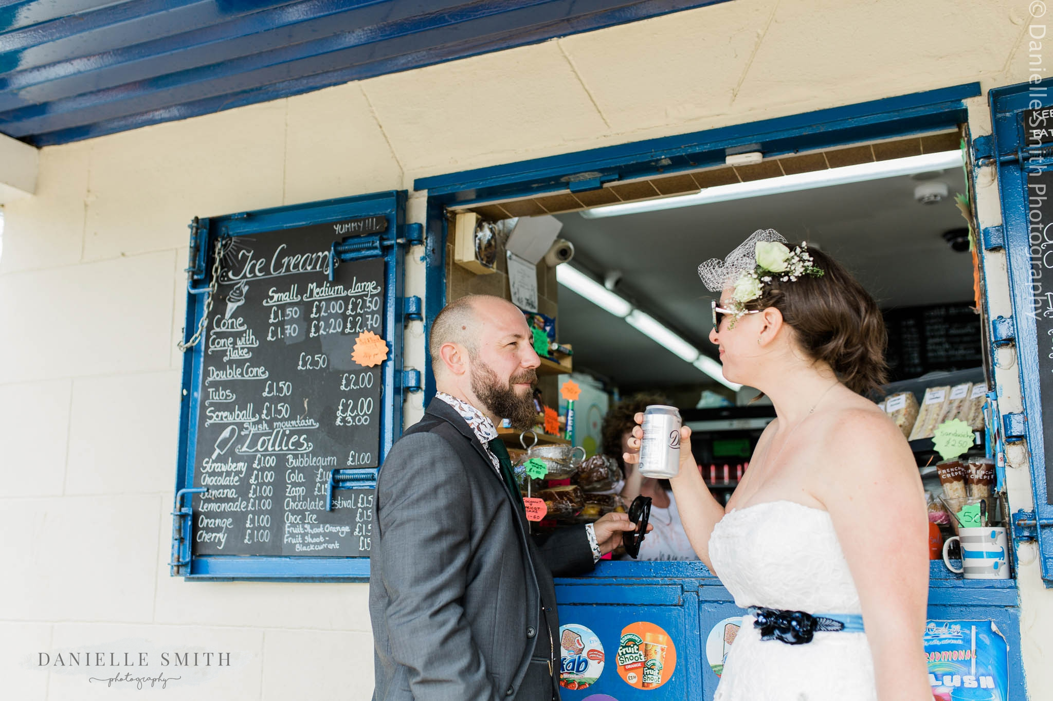 bride and groom buying can of coke from kiosk