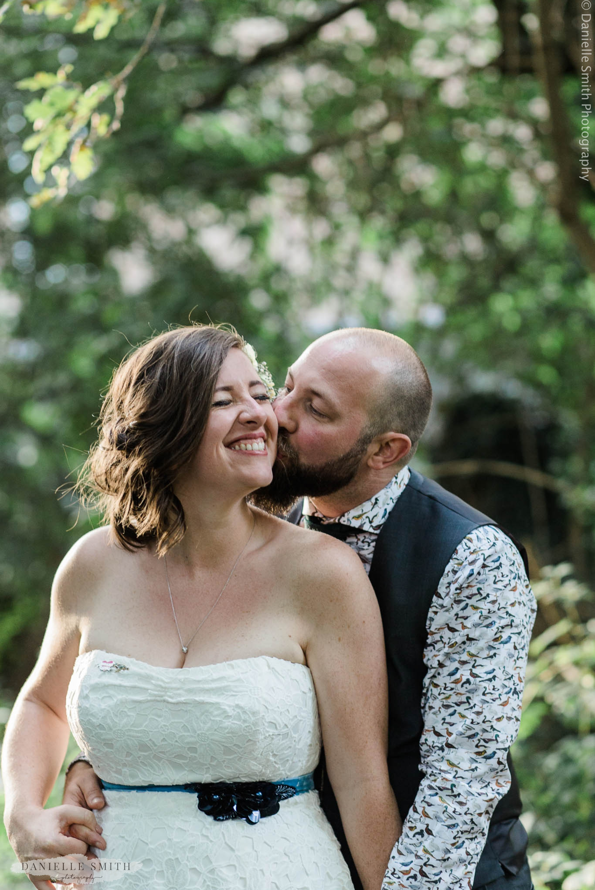groom kissing brides cheek - relaxed and fun wedding