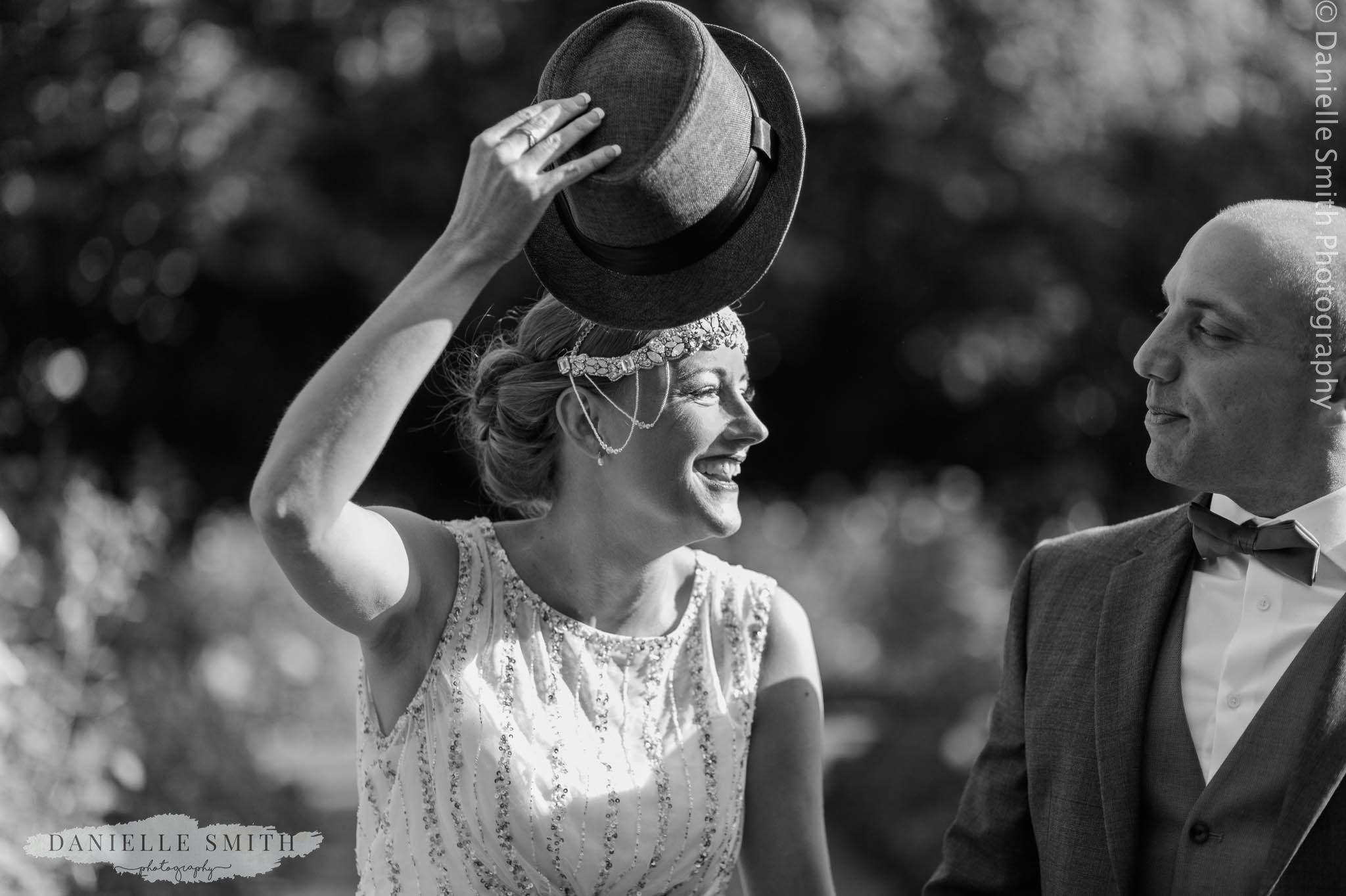 bride stealing grooms hat at gatsby wedding
