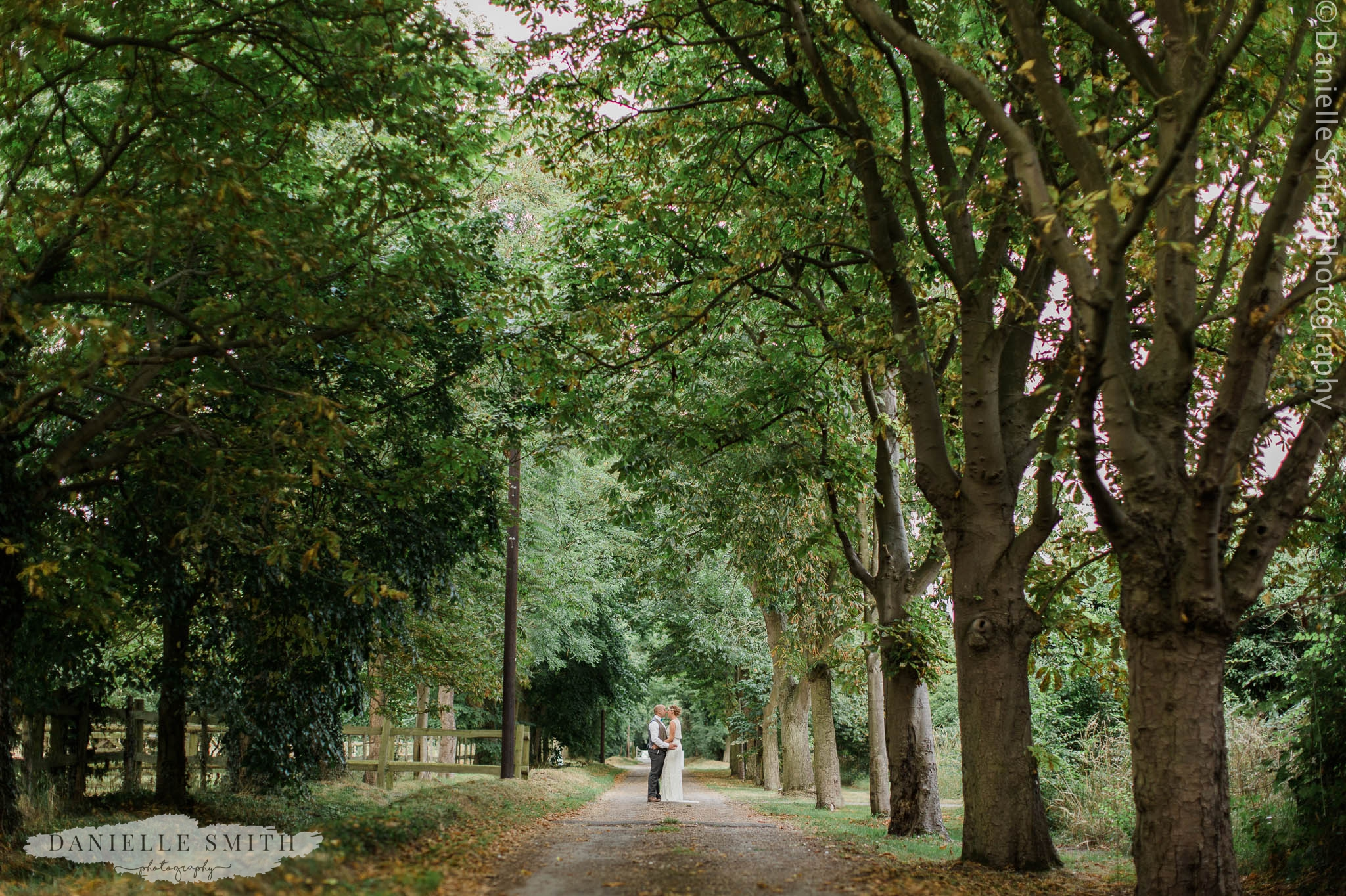 bride and groom in tunnel of trees at mangapp manor