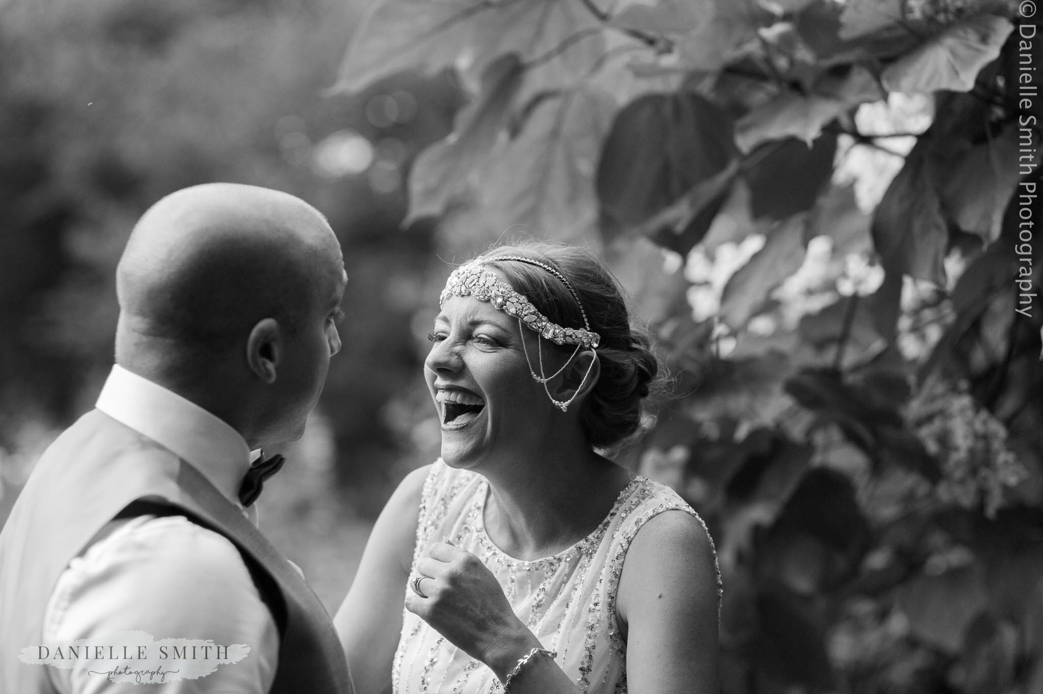 bride laughing at groom with 1920s style head piece