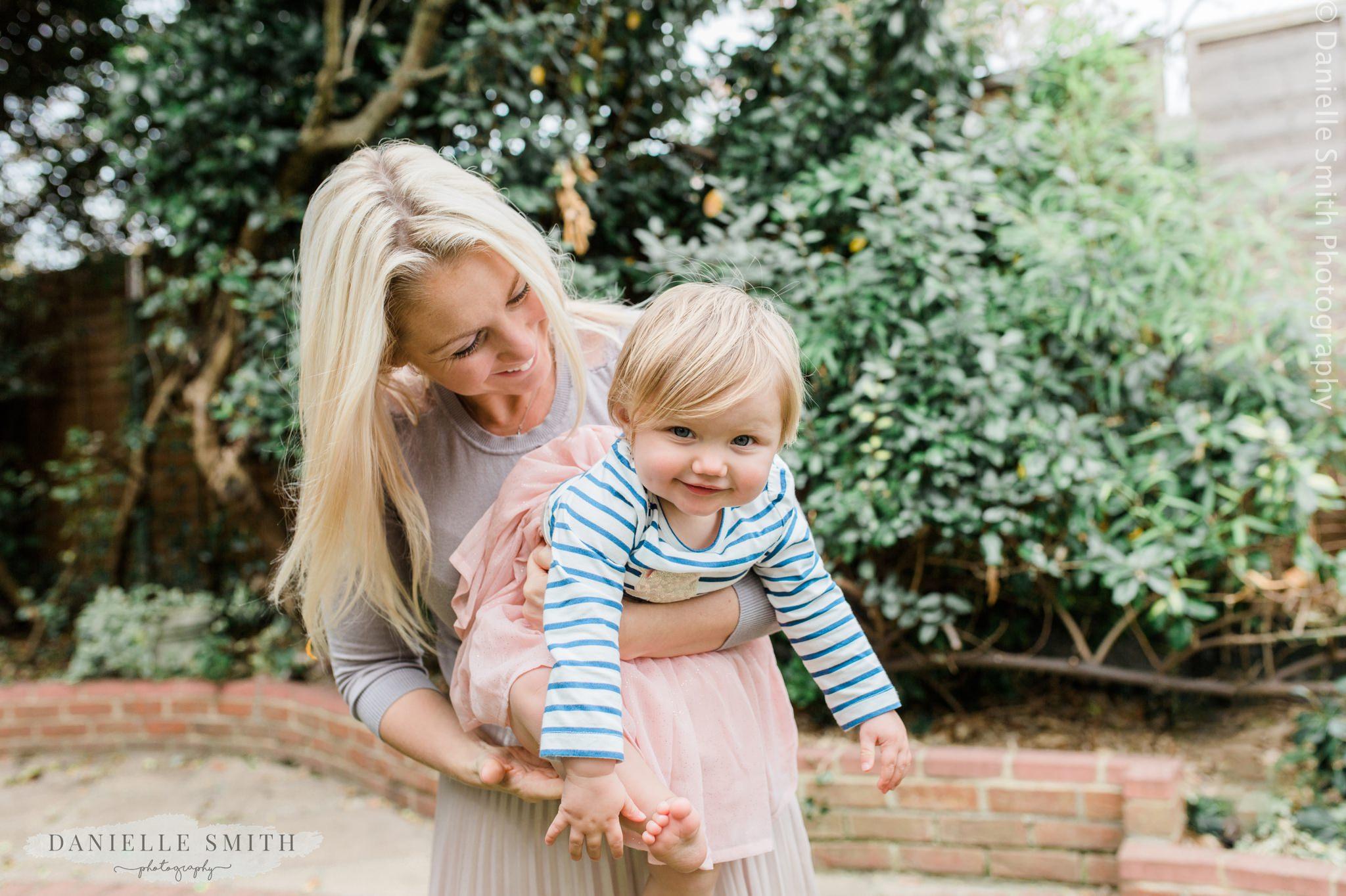 mum holding baby girl in garden - first birthday photos
