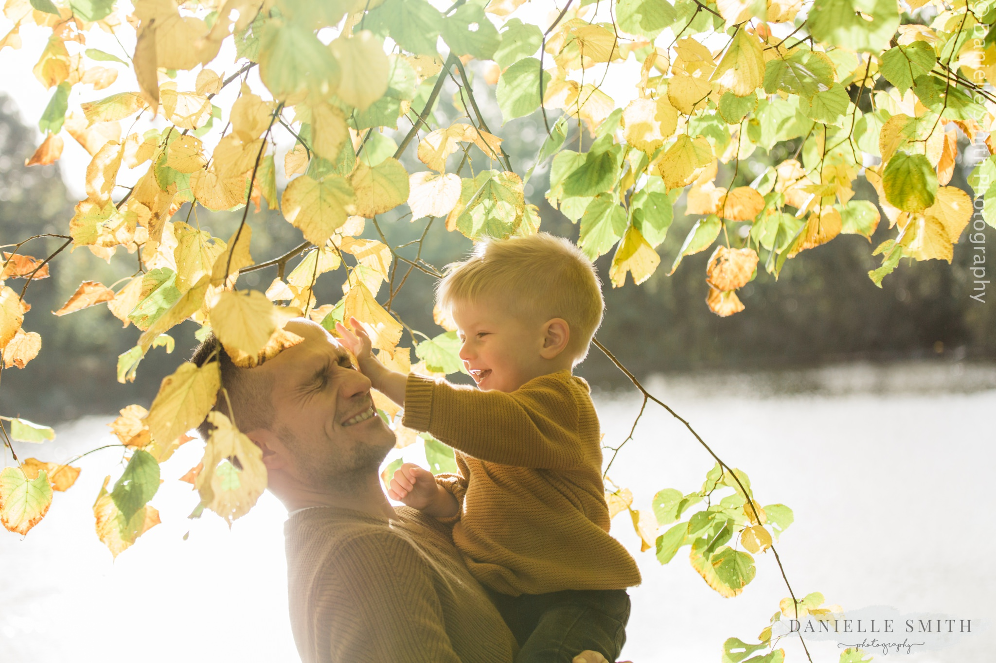 dad playing with his boy in autumn photo shoot boy poking dad in the eye - family photography