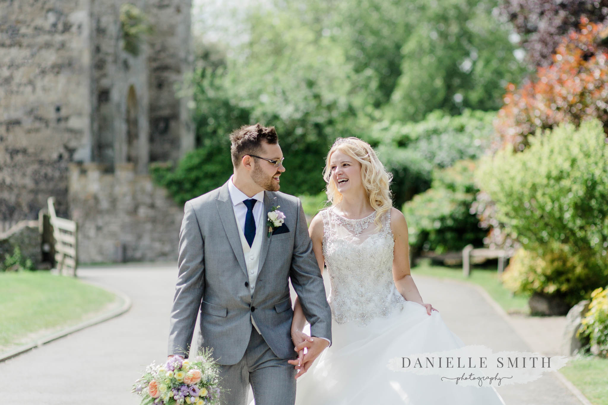 bride and groom walking and laughing - kent wedding photography