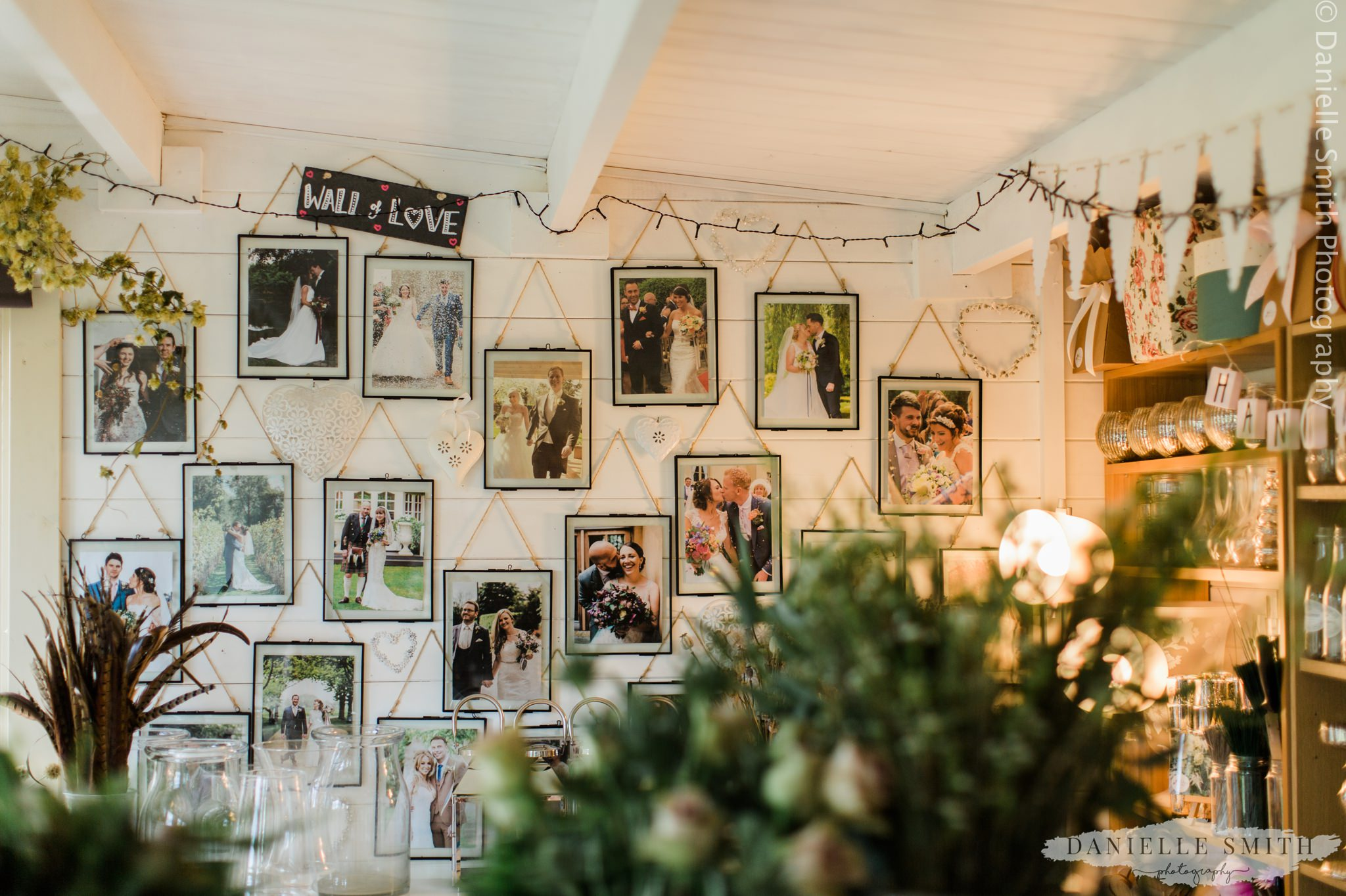 photos hanging on wall in wedding florist workshop