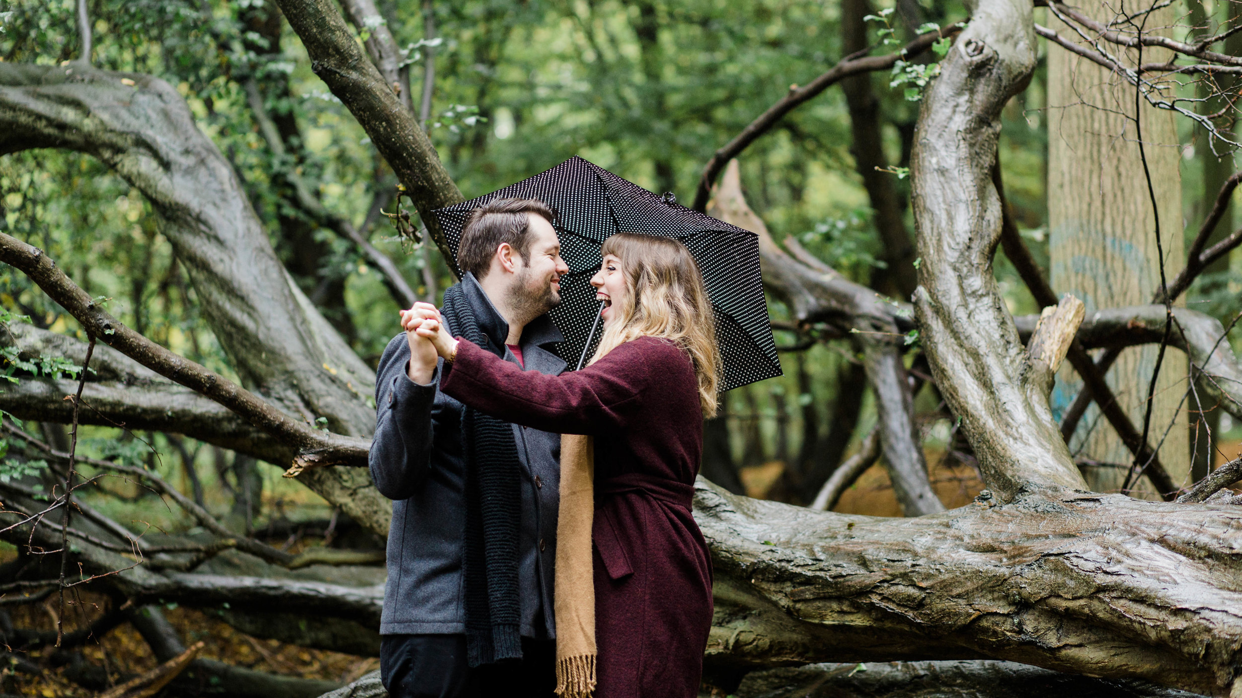 couple laughing in woods in autumn - pre-wedding photography