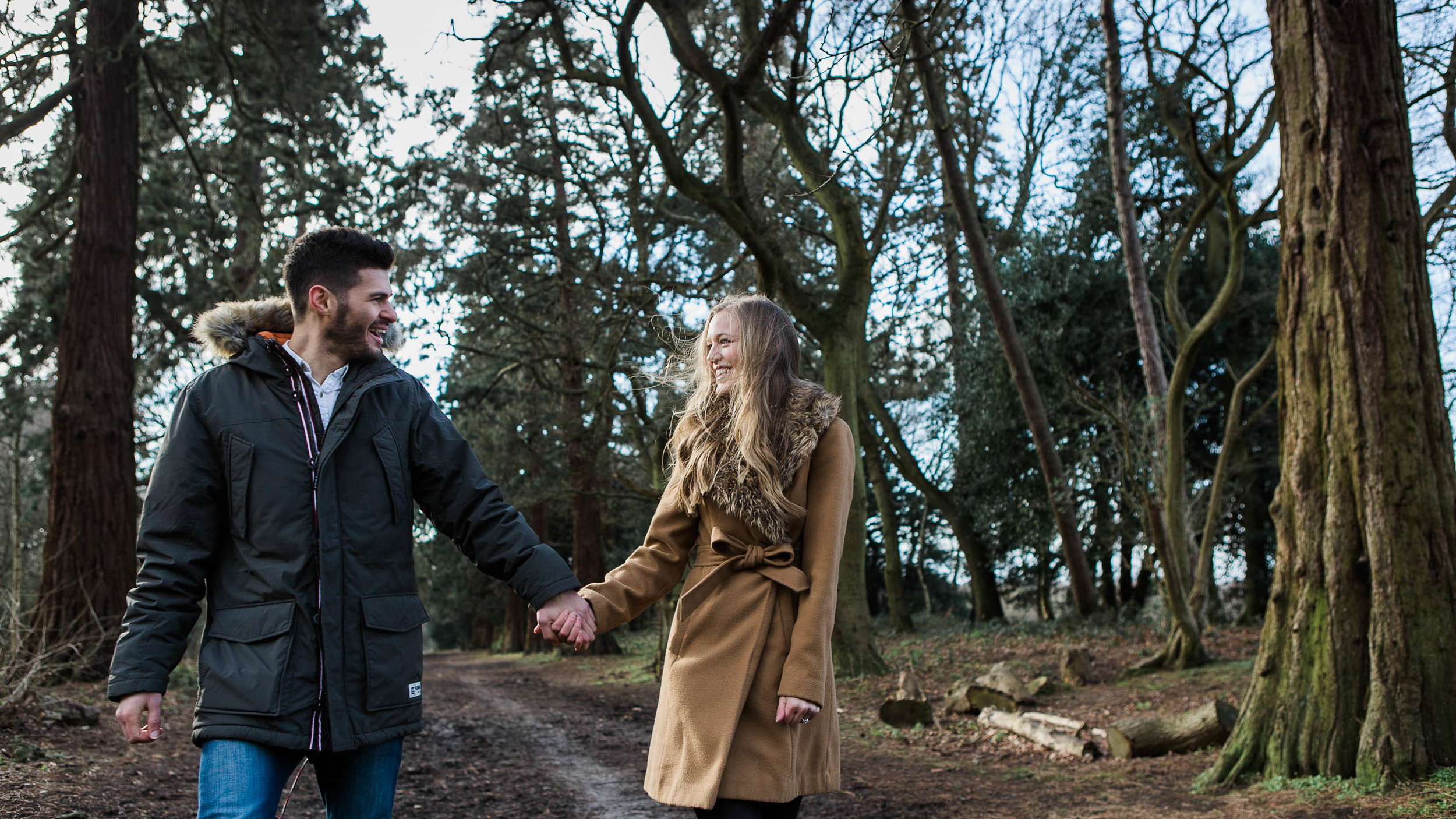 couple walking holding hands in woods