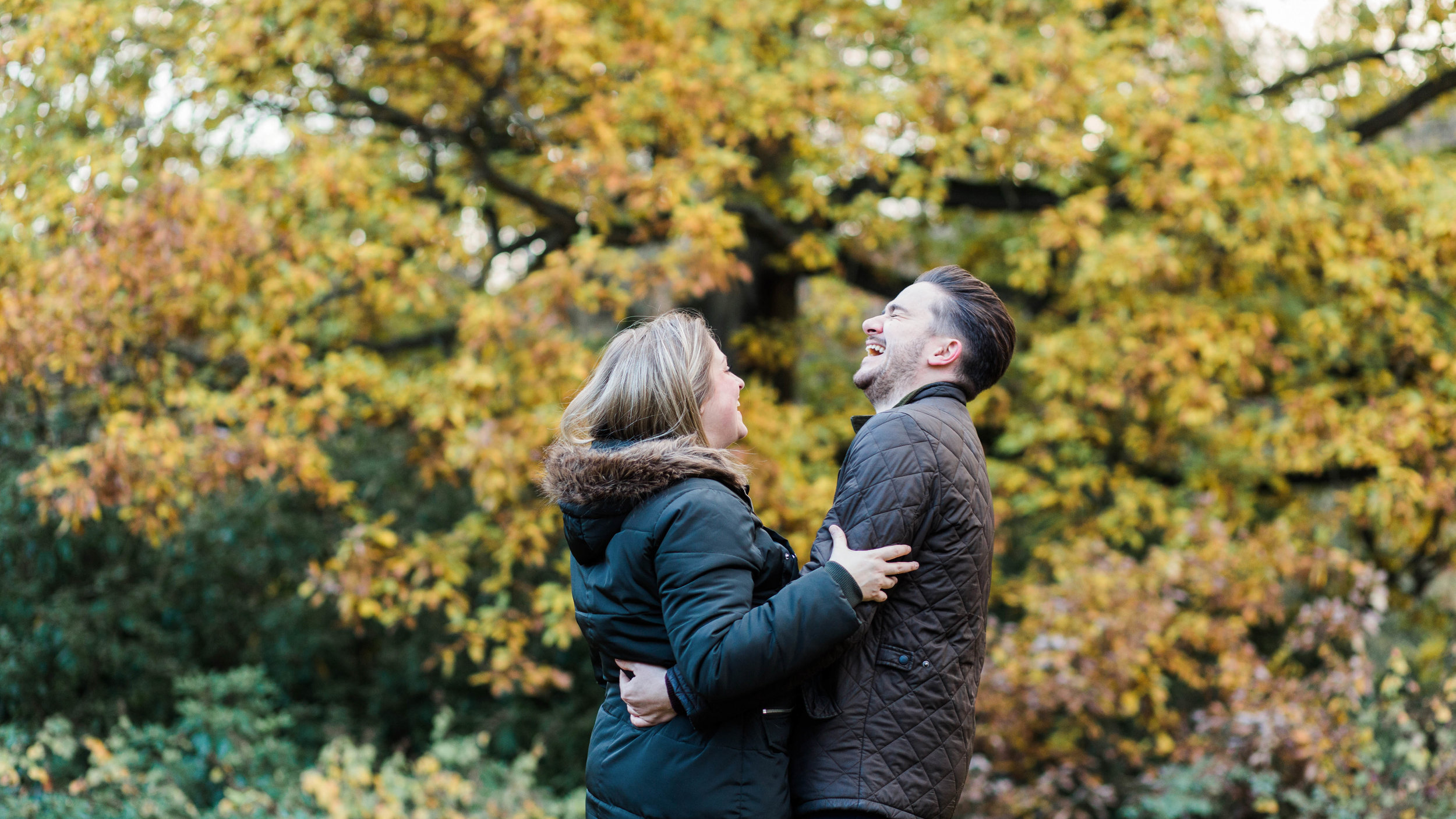 couple laughing with autumn leaves in background