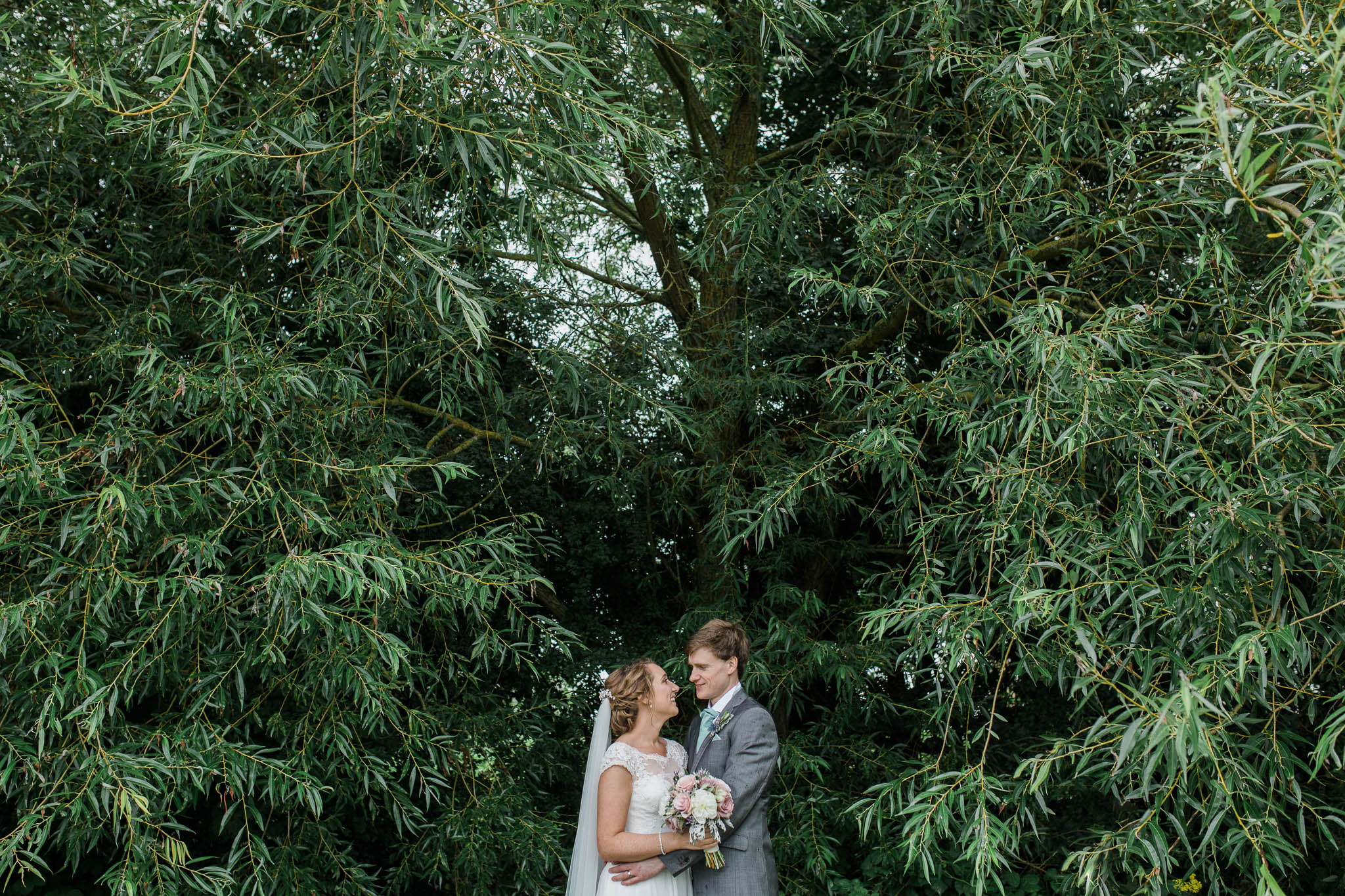 bride and groom under tree in rain