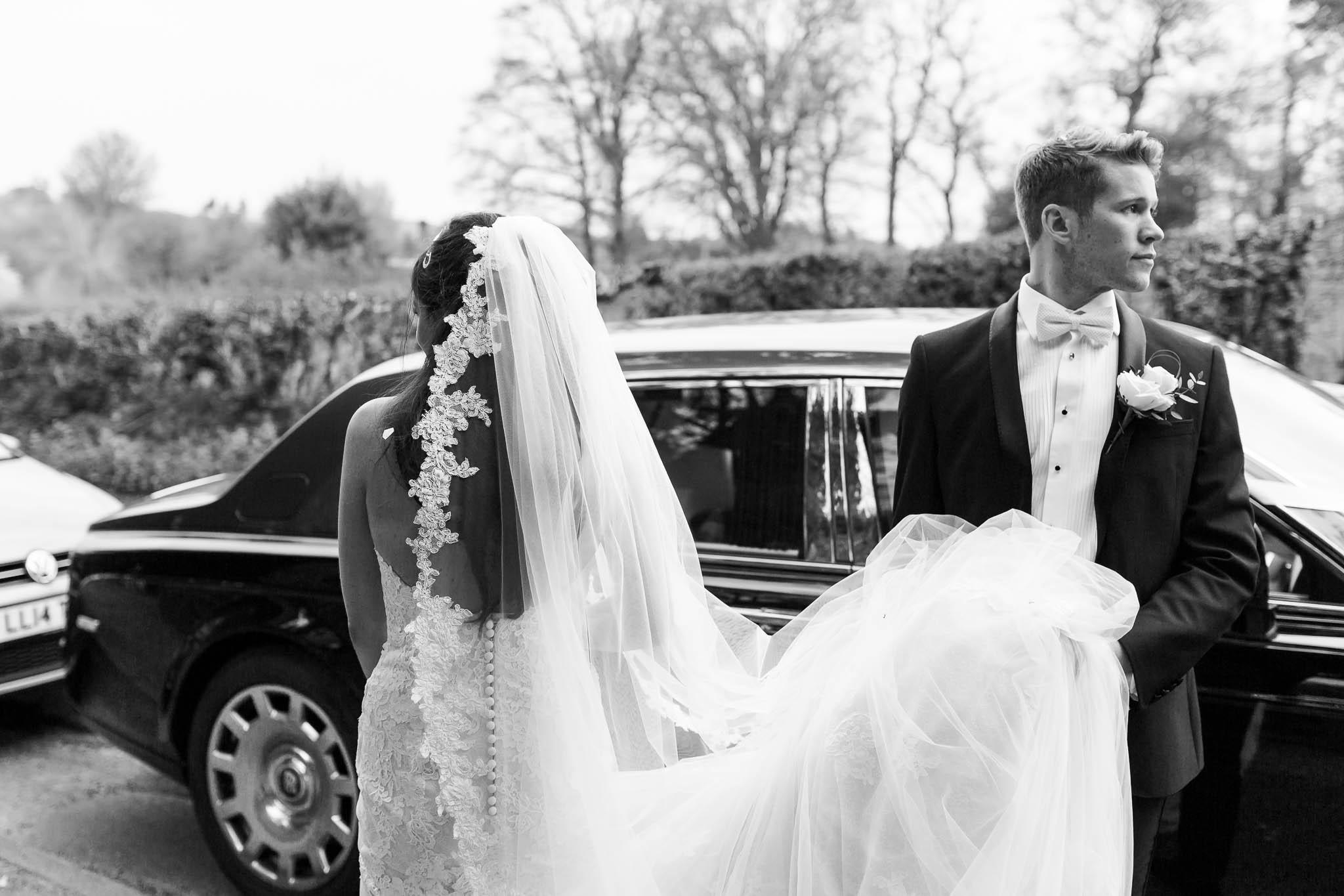 bride and groom getting in wedding car