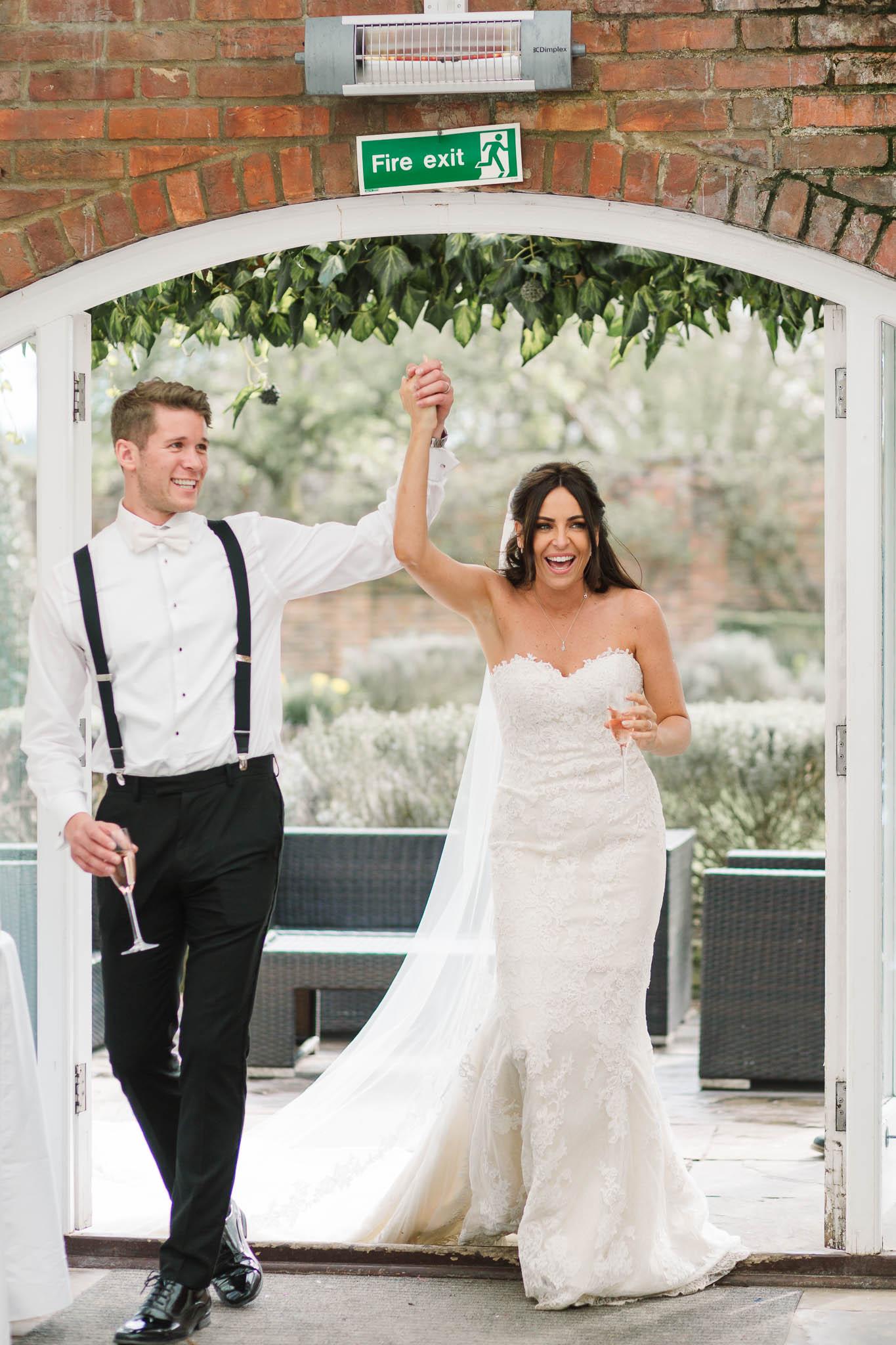 bride and groom entering reception room