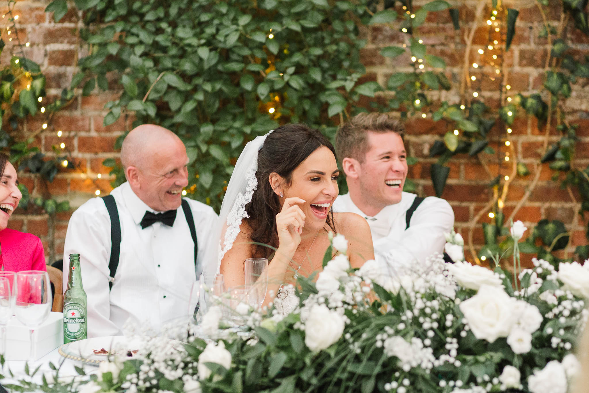 bride and groom laughing at speeches at northbrook park wedding venue