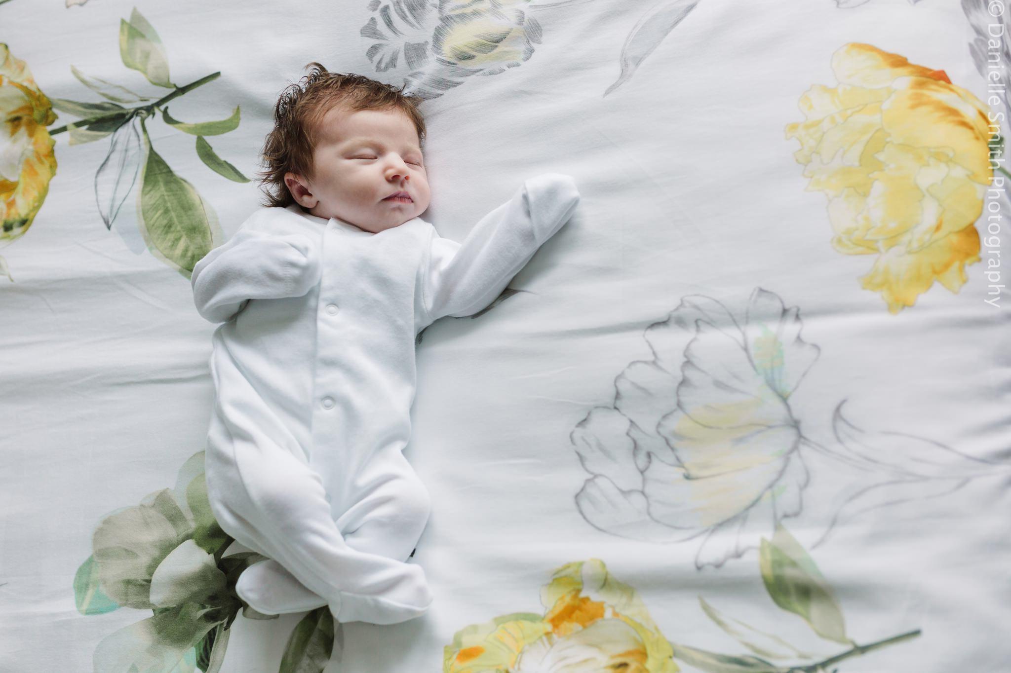 newborn baby in baby grow on bed