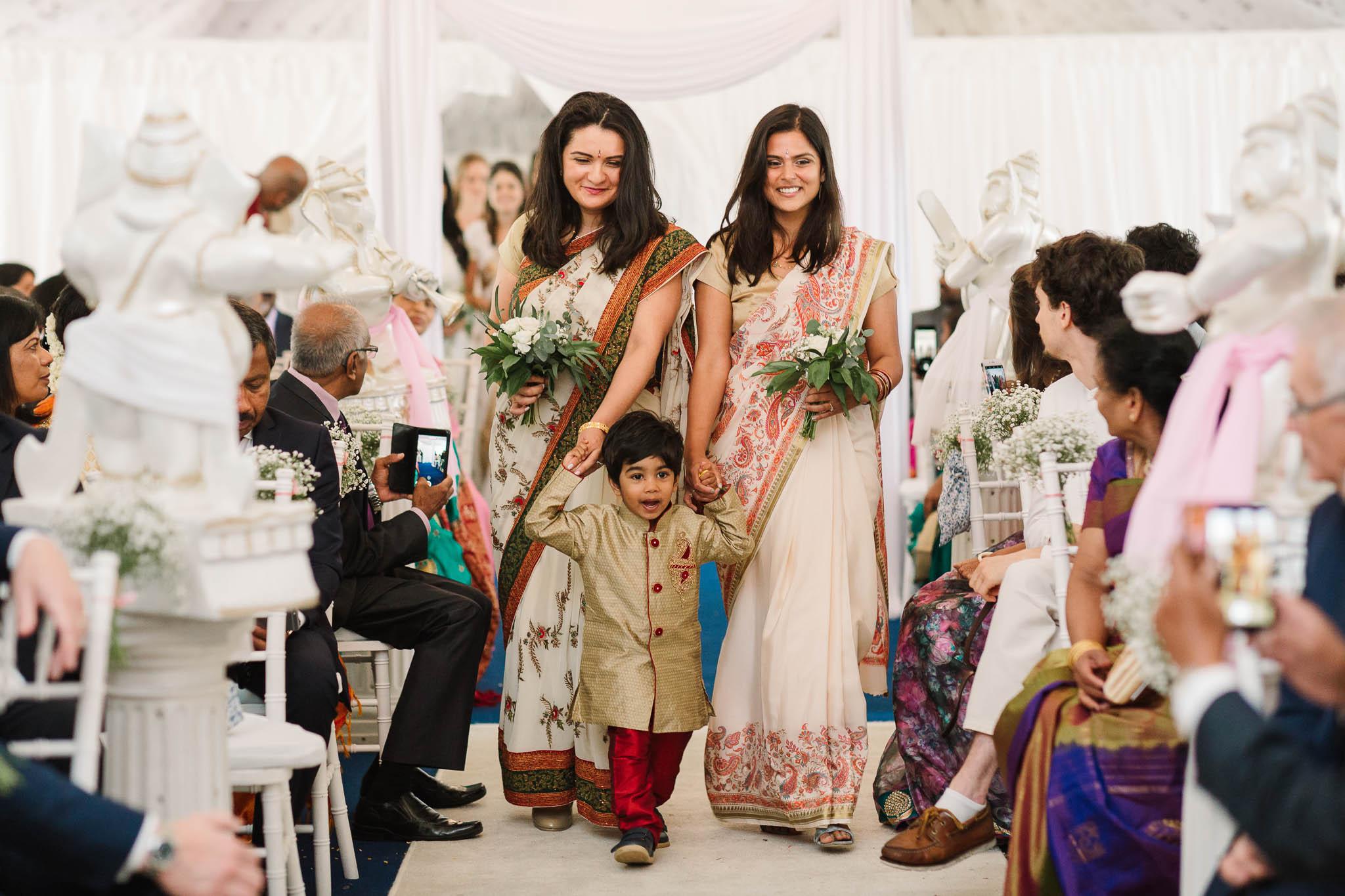 bridesmaids and page boy walking down aisle at indian wedding