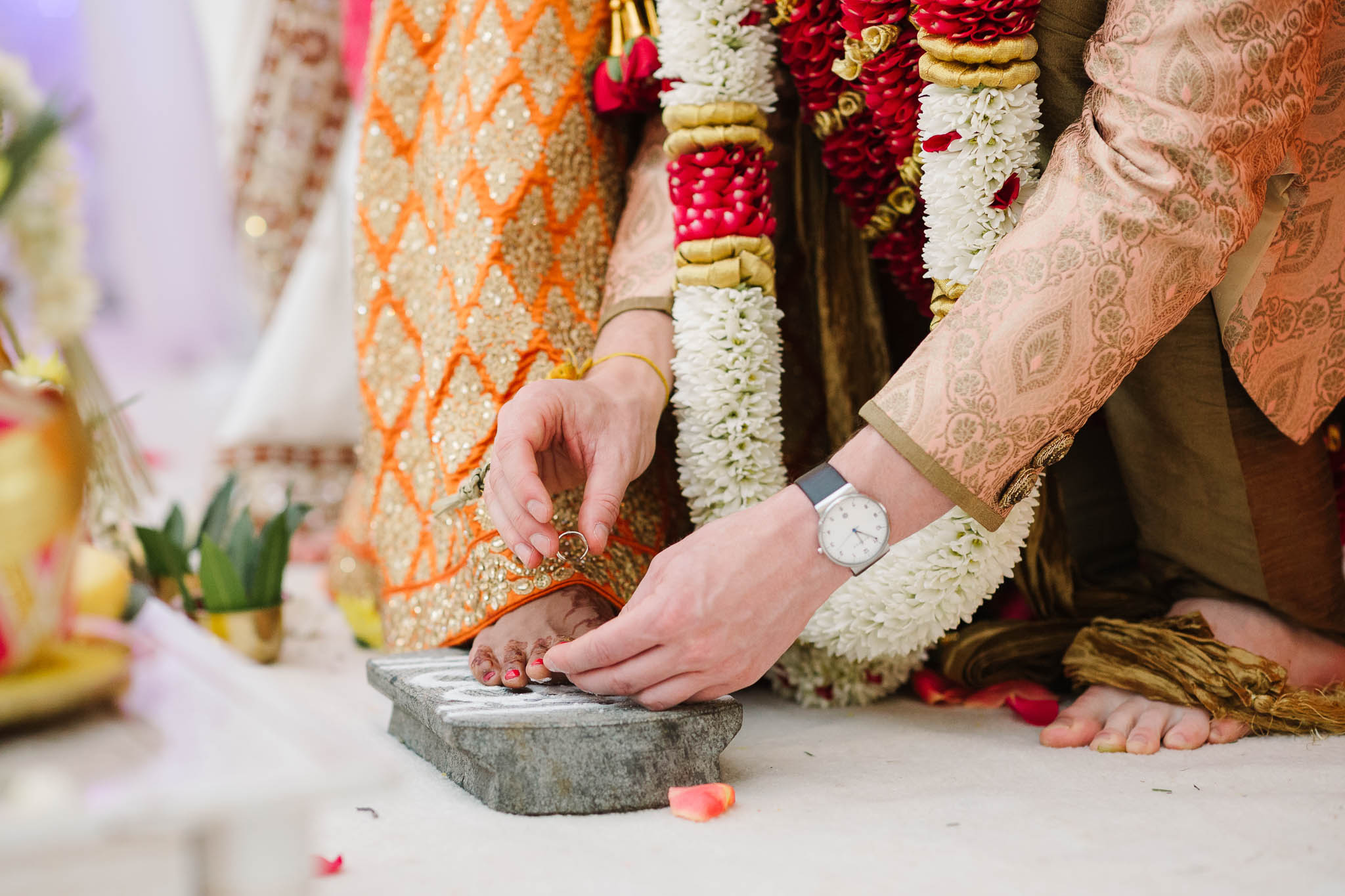 groom putting toe ring on brides foot