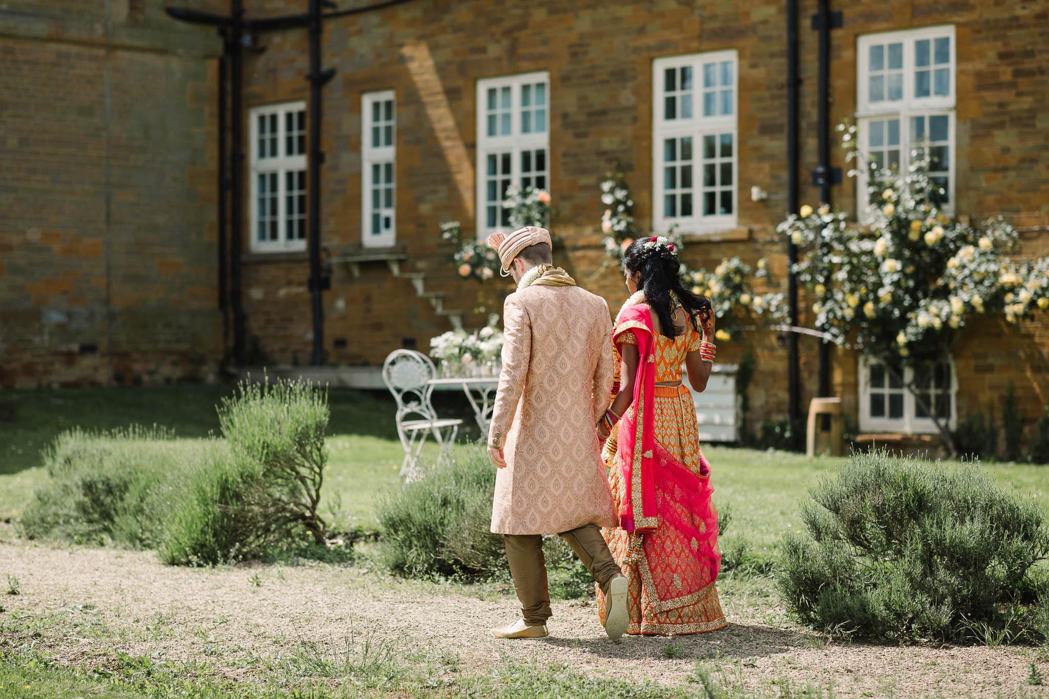 indina bride and groom walking through gardens