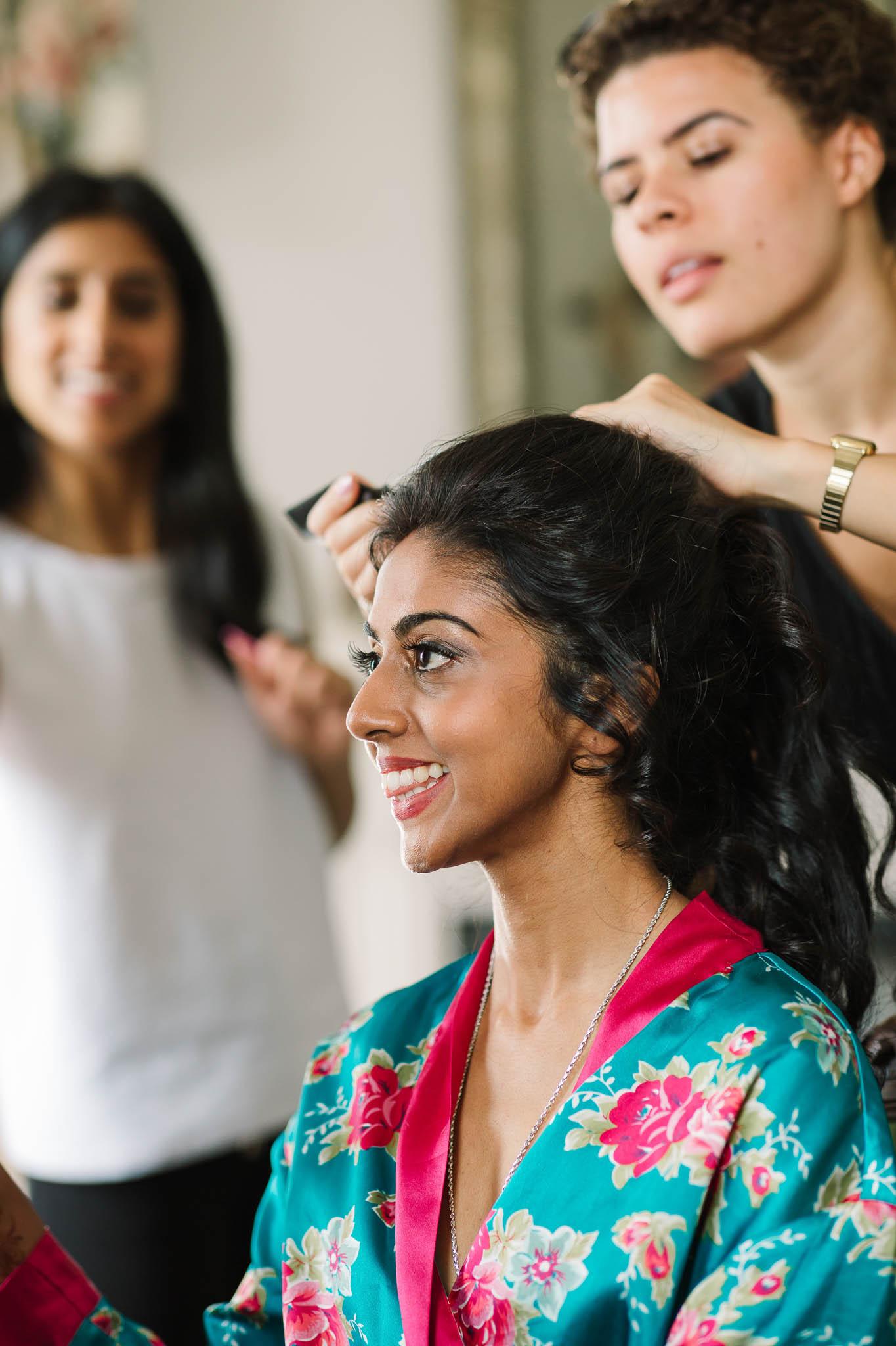 bride getting hair done at wedding