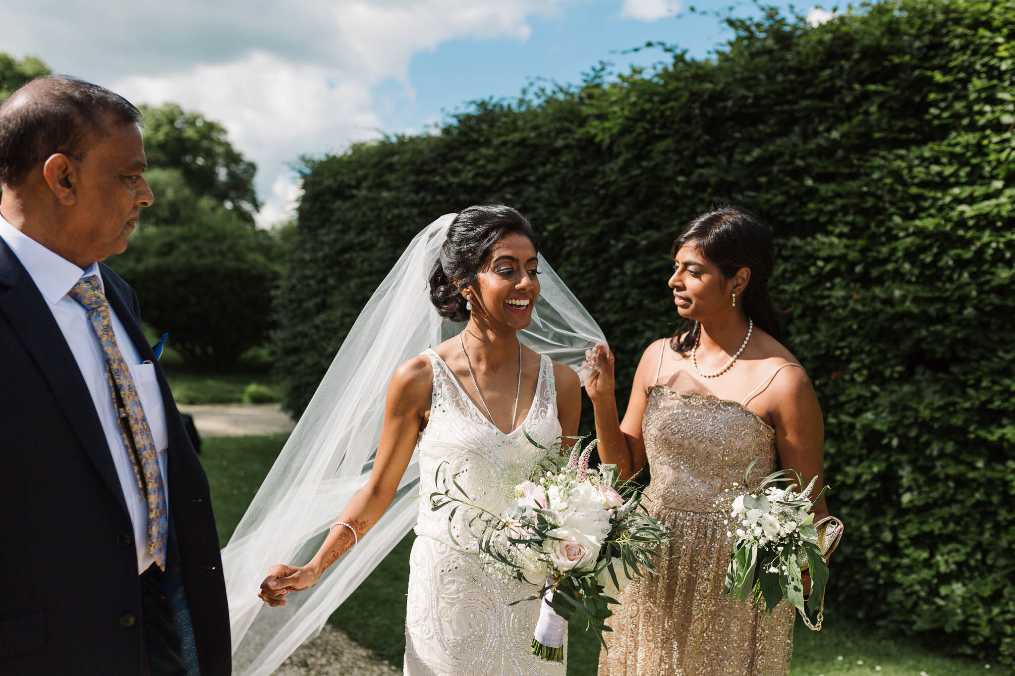 bride and her sister fixing veil