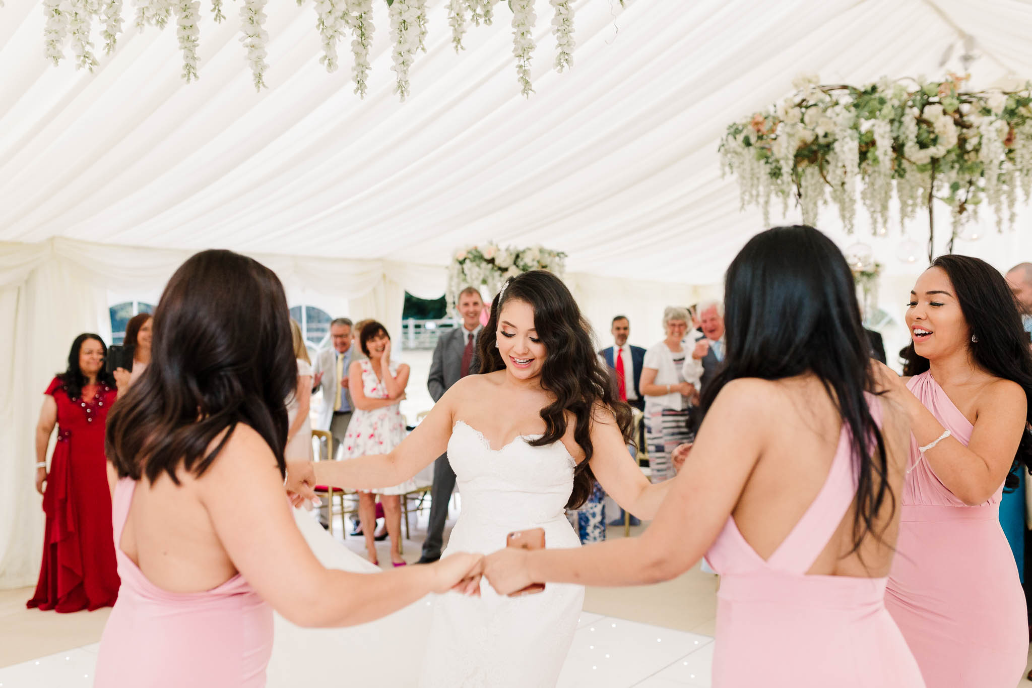 bride dancing with bridesmaids at fun and relaxed summer wedding