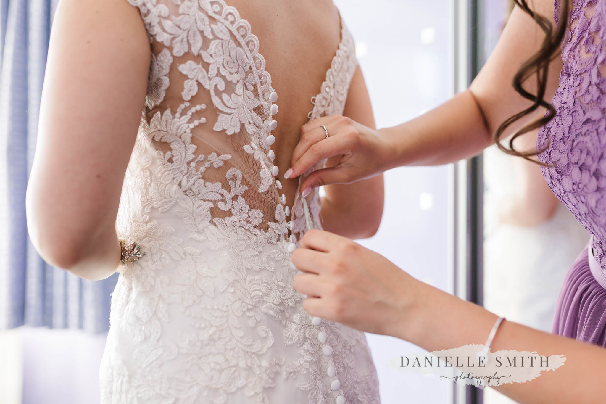 bridesmaid doing up back of brides lace dress