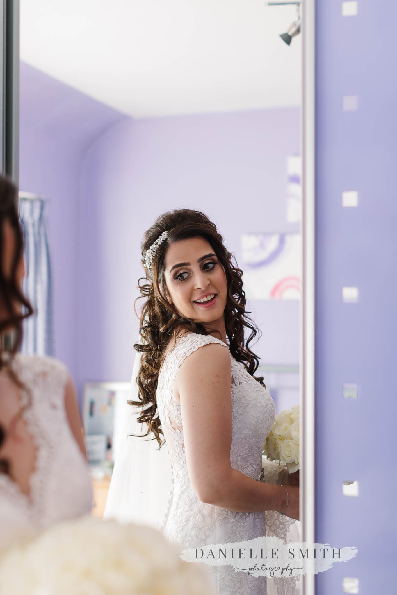 bride looking at back of dress in mirror