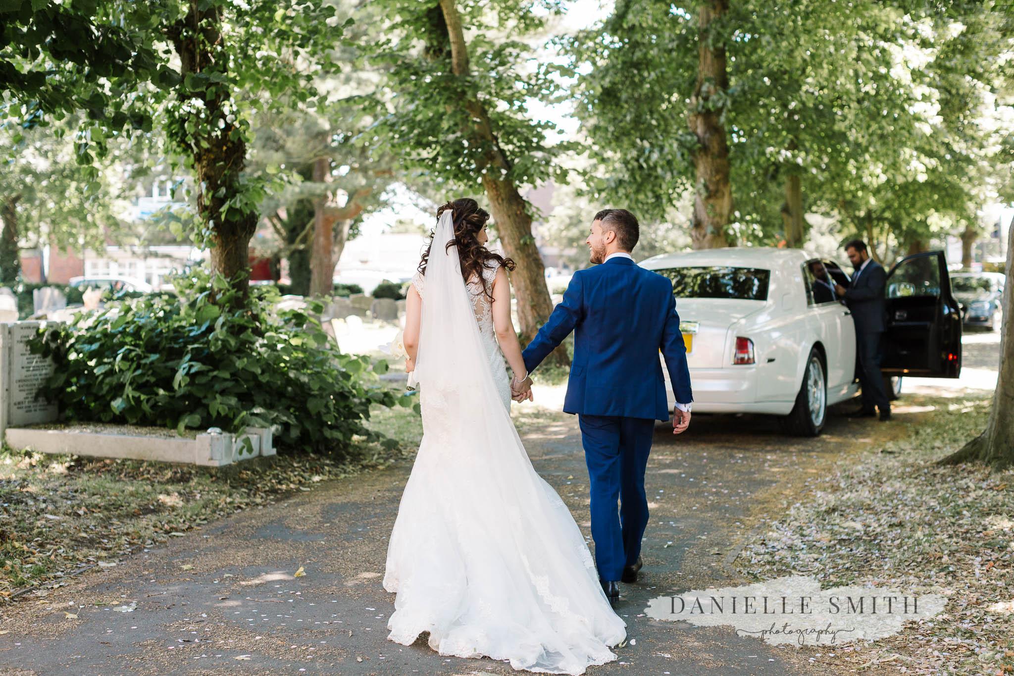 bride and groom walking towards wedding car