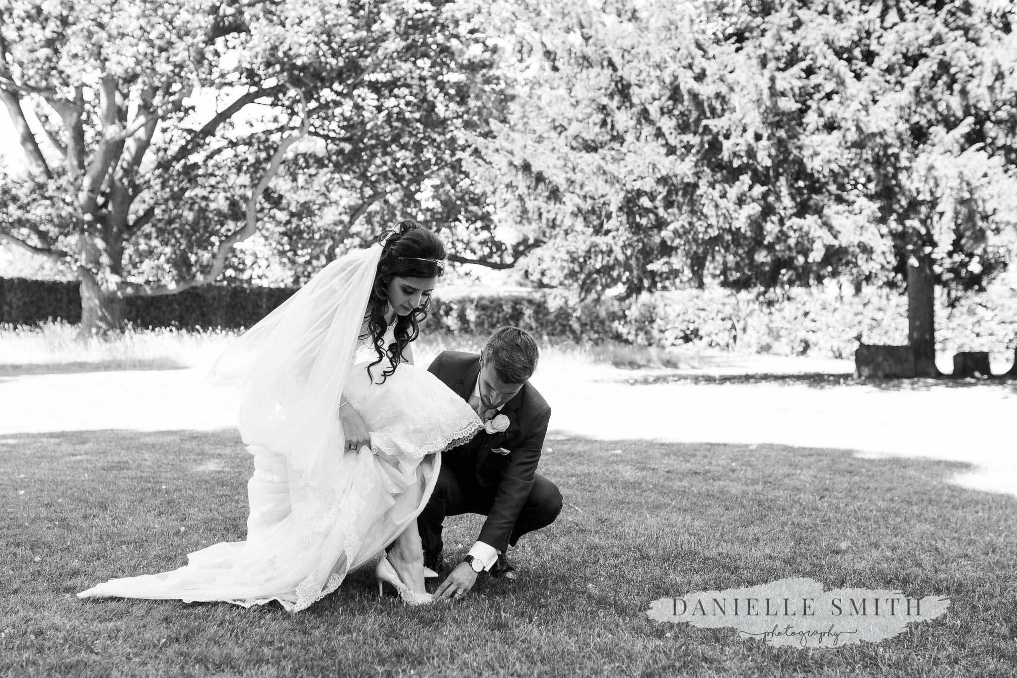 groom helping bride put her shoes on