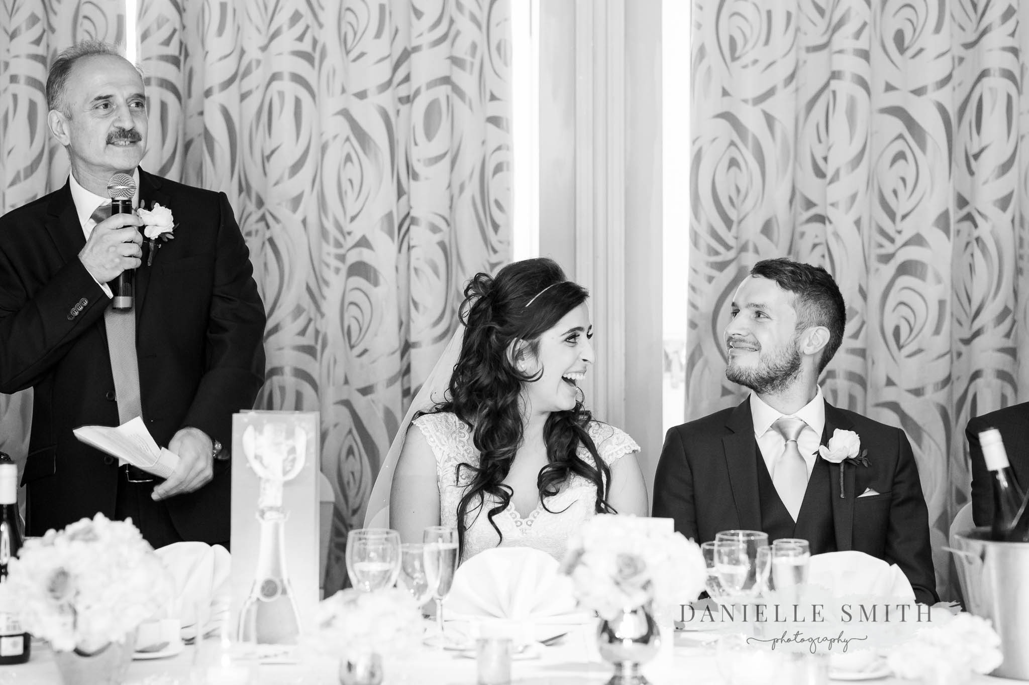 father of bride and bride and groom laughing at speeches