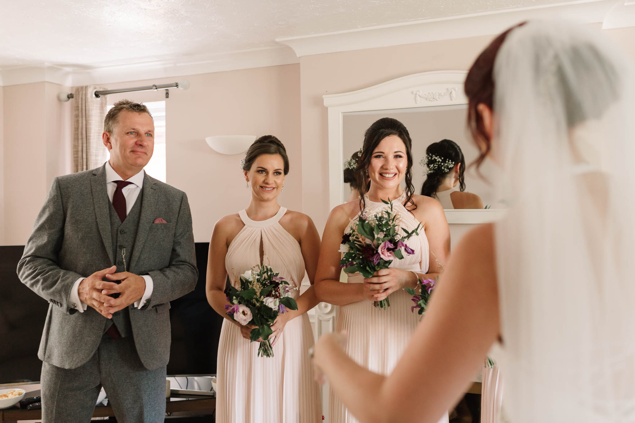 bridesmaids and Dad seeing bride in her dress
