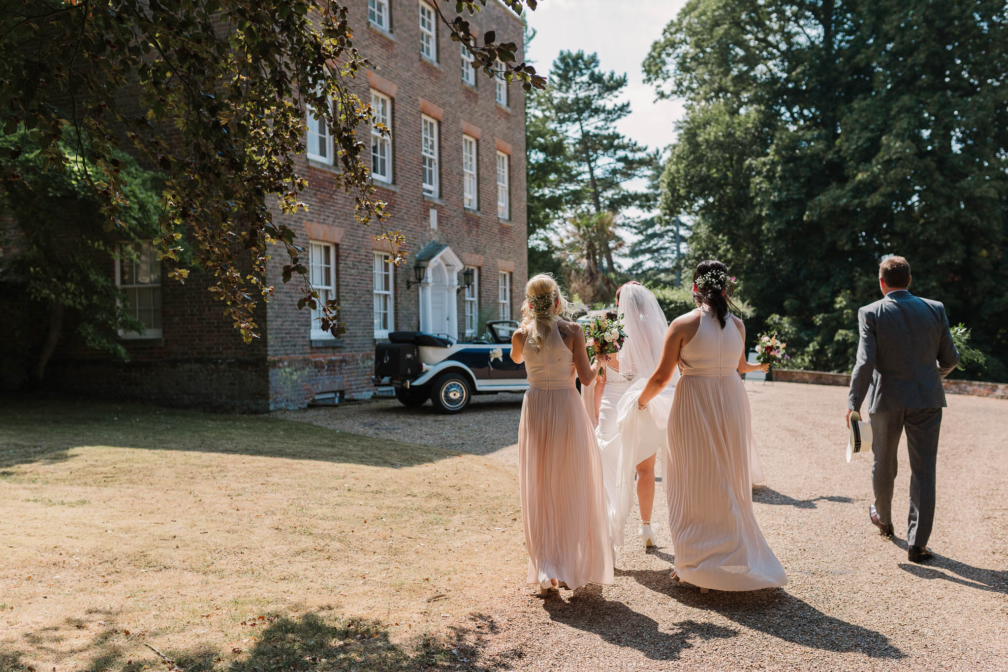 bride and bridesmaids walking to cars