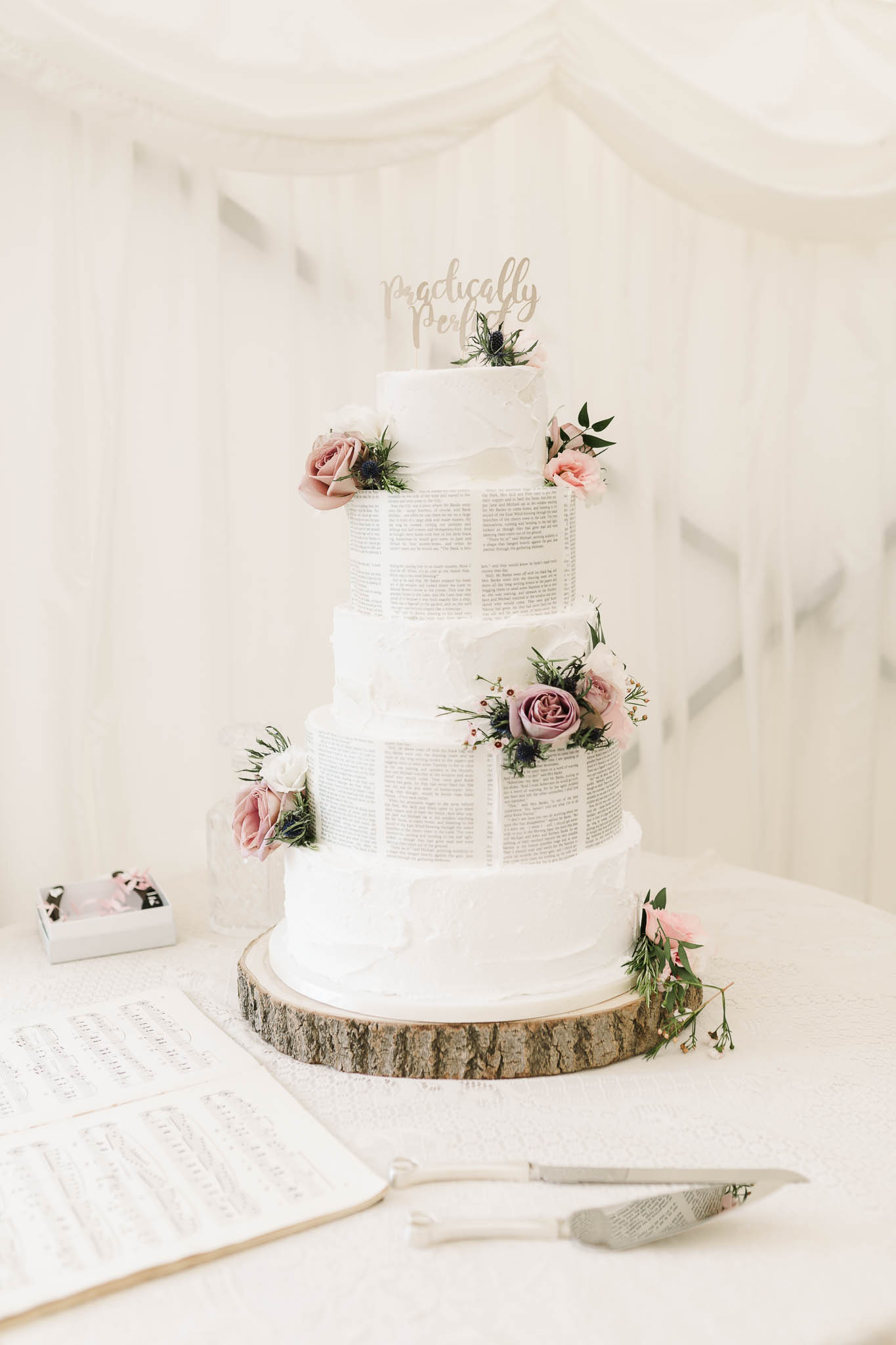 white wedding cake with book pages
