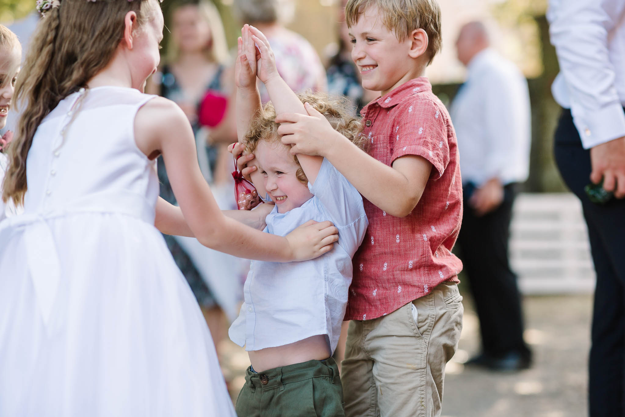 kids tickling each other at wedding