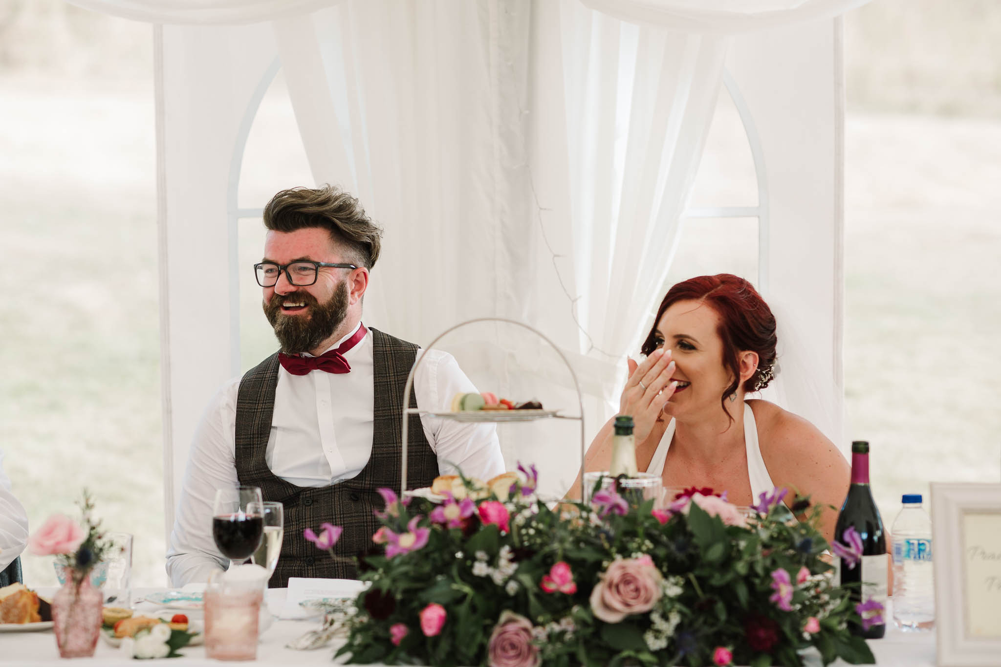 bride and groom laughing at dads speech