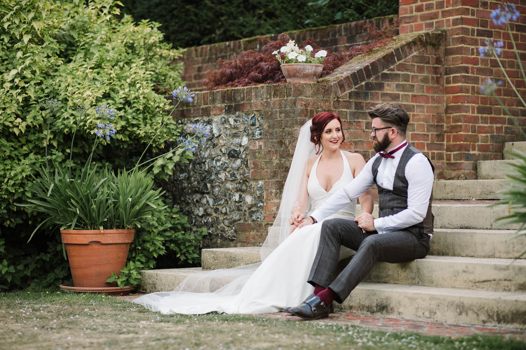 bride and groom sitting in steps at swarling manor