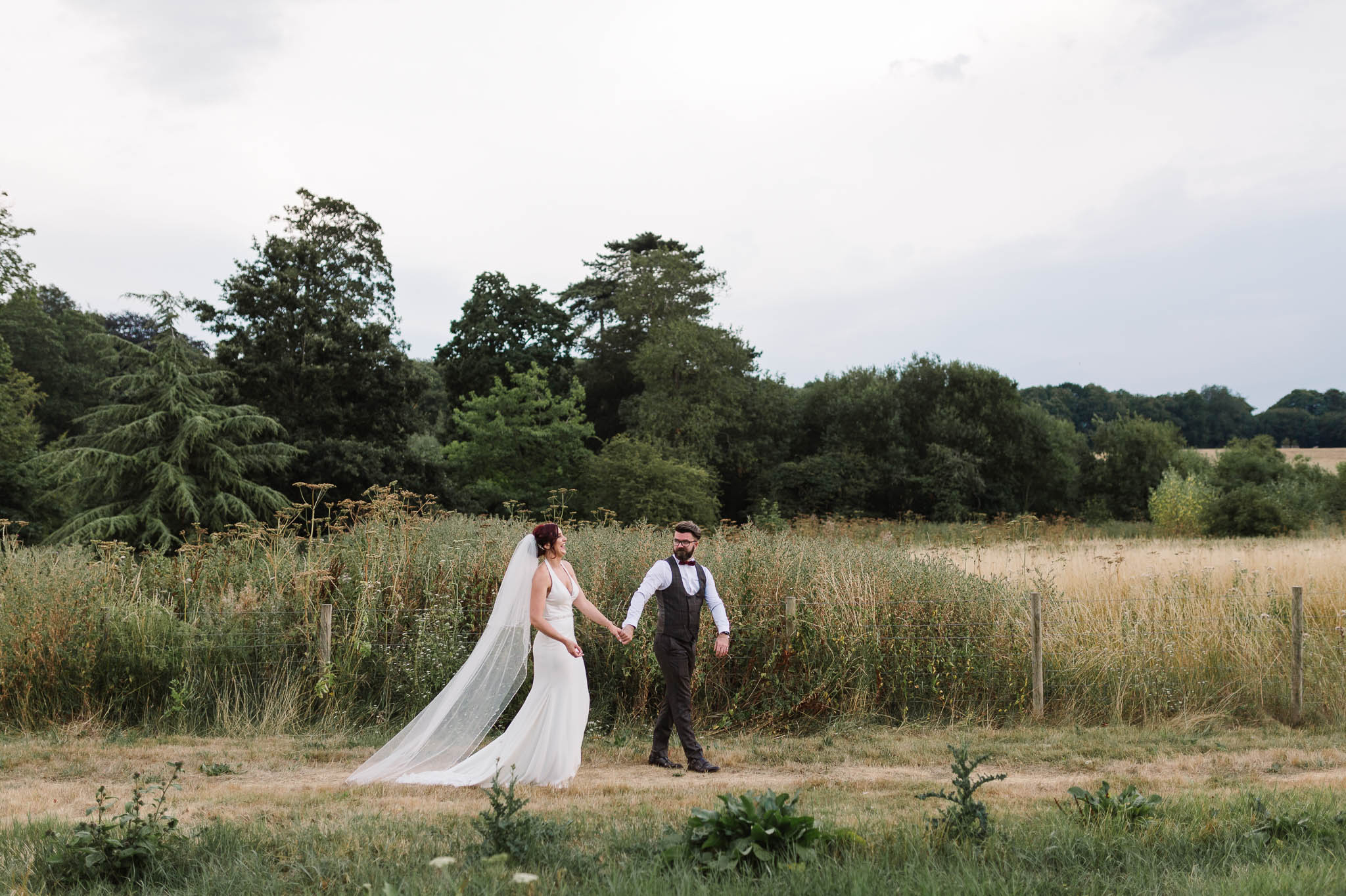 bride and groom walking through countryside