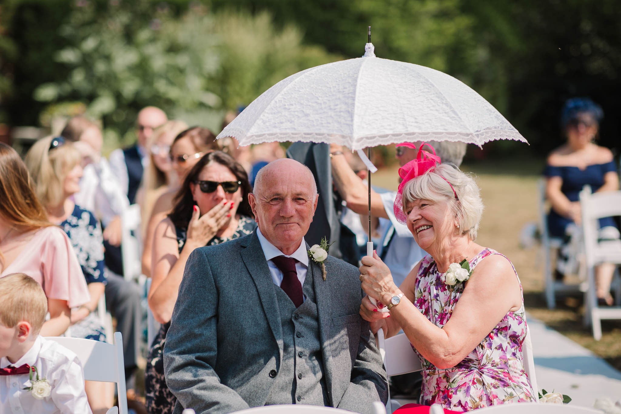 parents with umbrella at sunny summer wedding