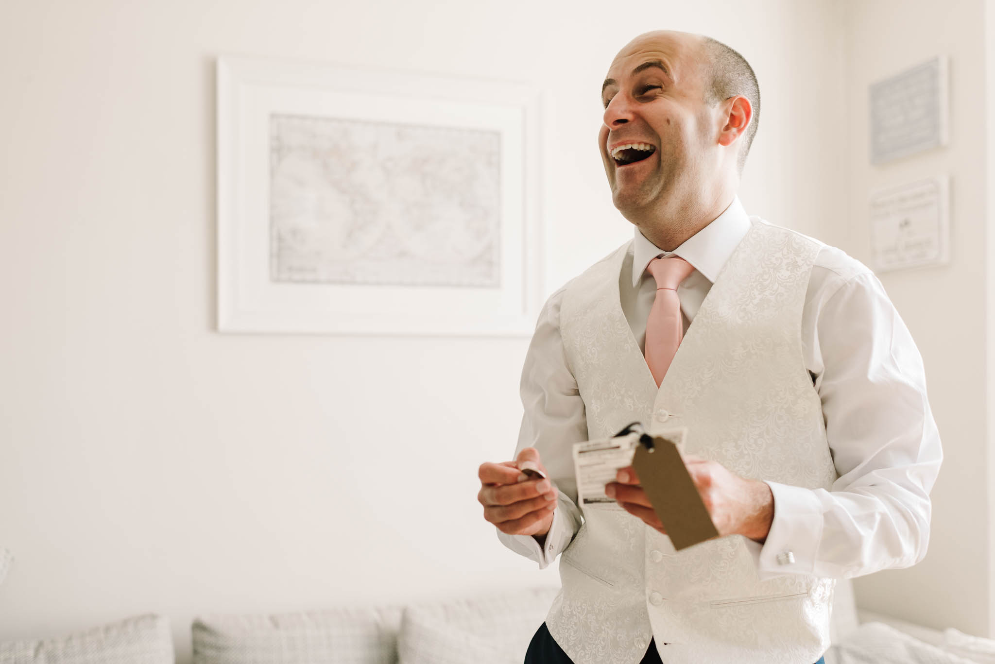 groom laughing opening wedding present