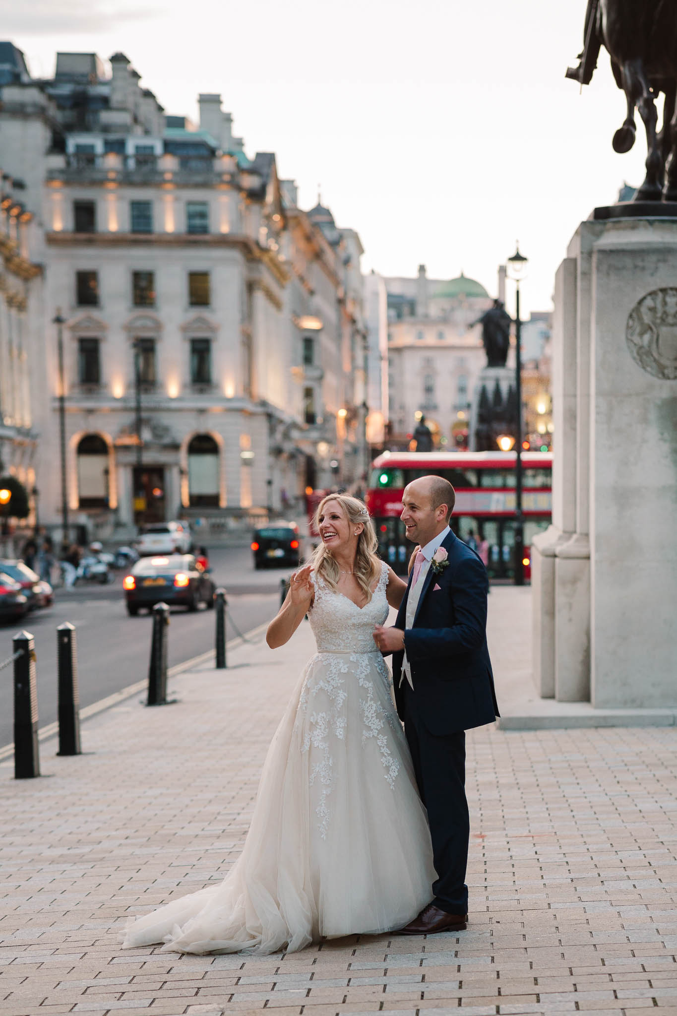 bride and groom waving at passers by in London