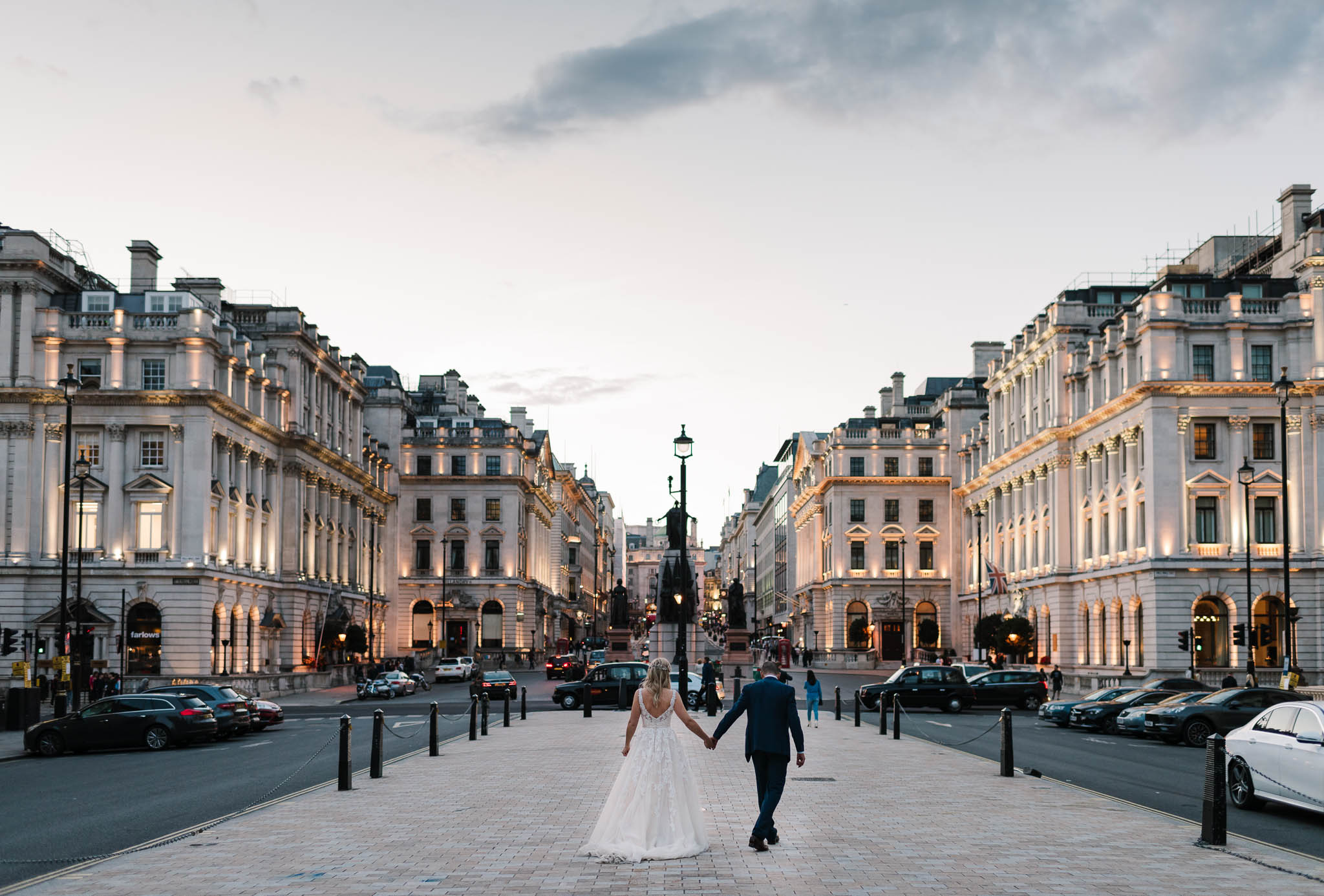 bride and groom walking through Pall Mall at sunset- Elegant London Wedding at the Royal Automobile Club
