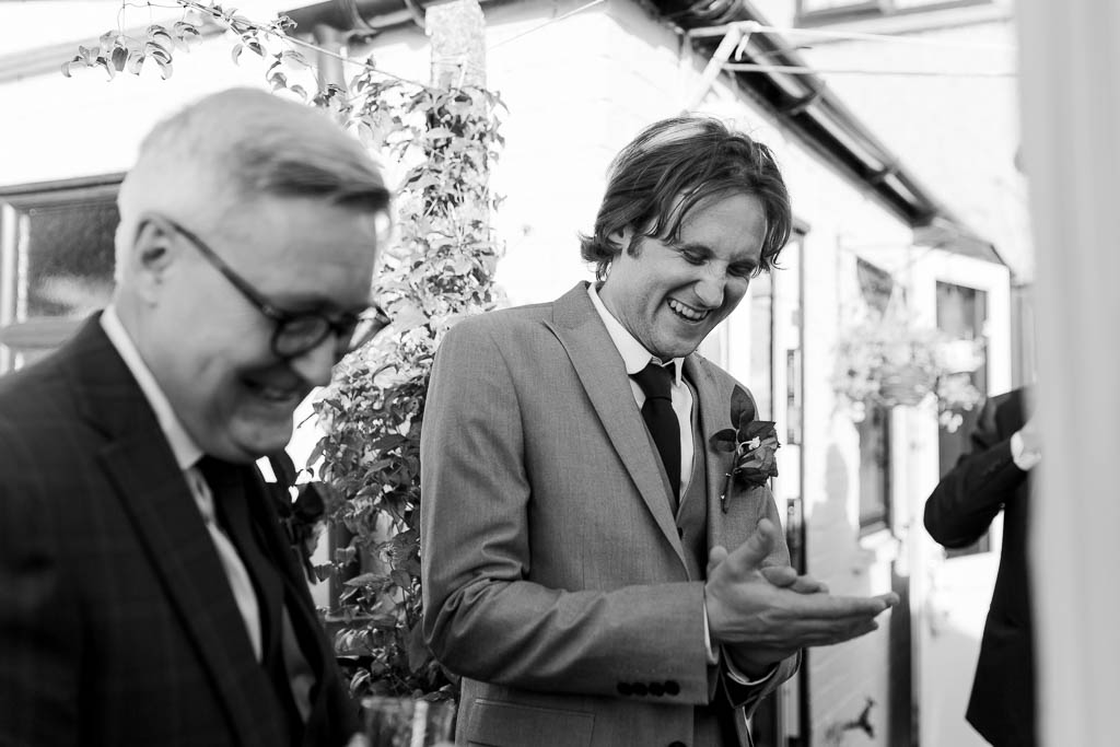 groom laughing at garden wedding
