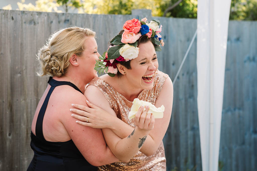 bride an bridesmaid hugging and laughing