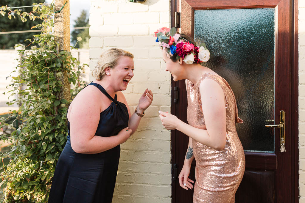 bride and bridemaid laughing at chilled garden wedding reception