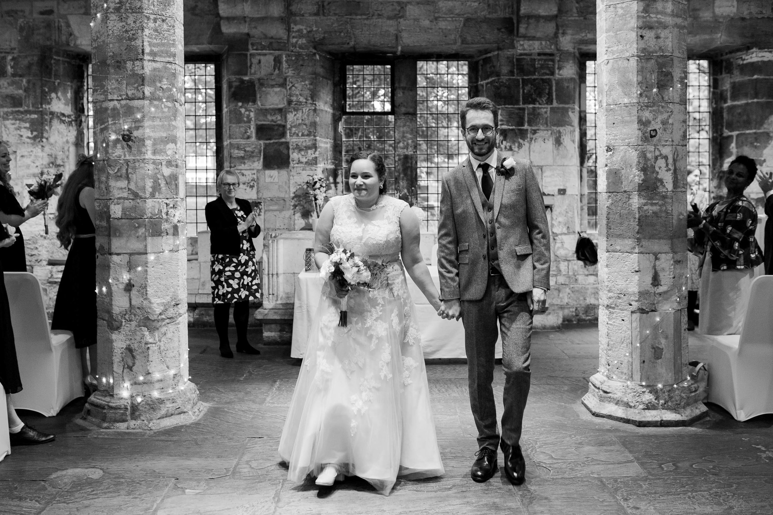 bride and groom walking down the aisle at the hospitium york