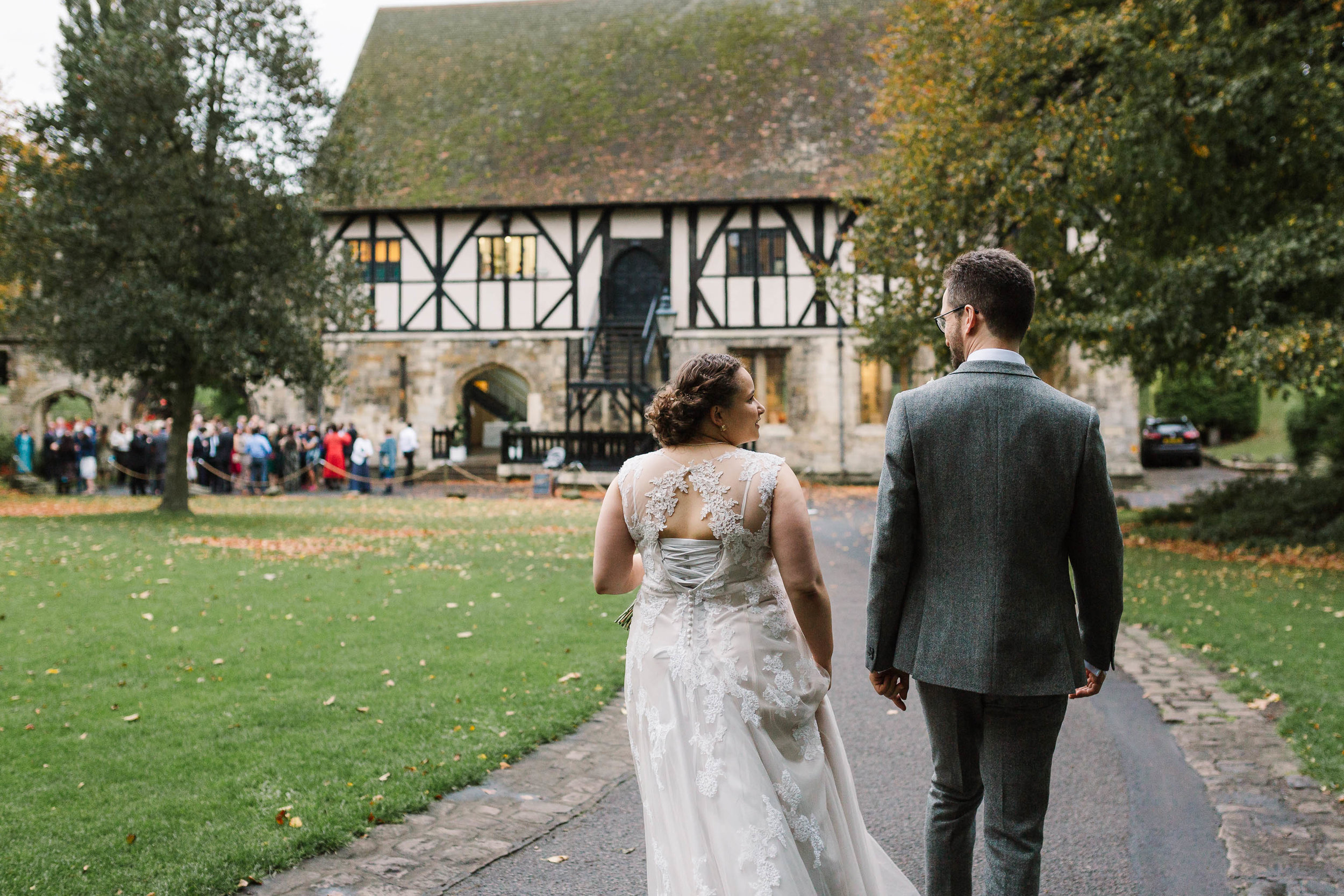 bride and groom walking towards their guests at the hospitium york