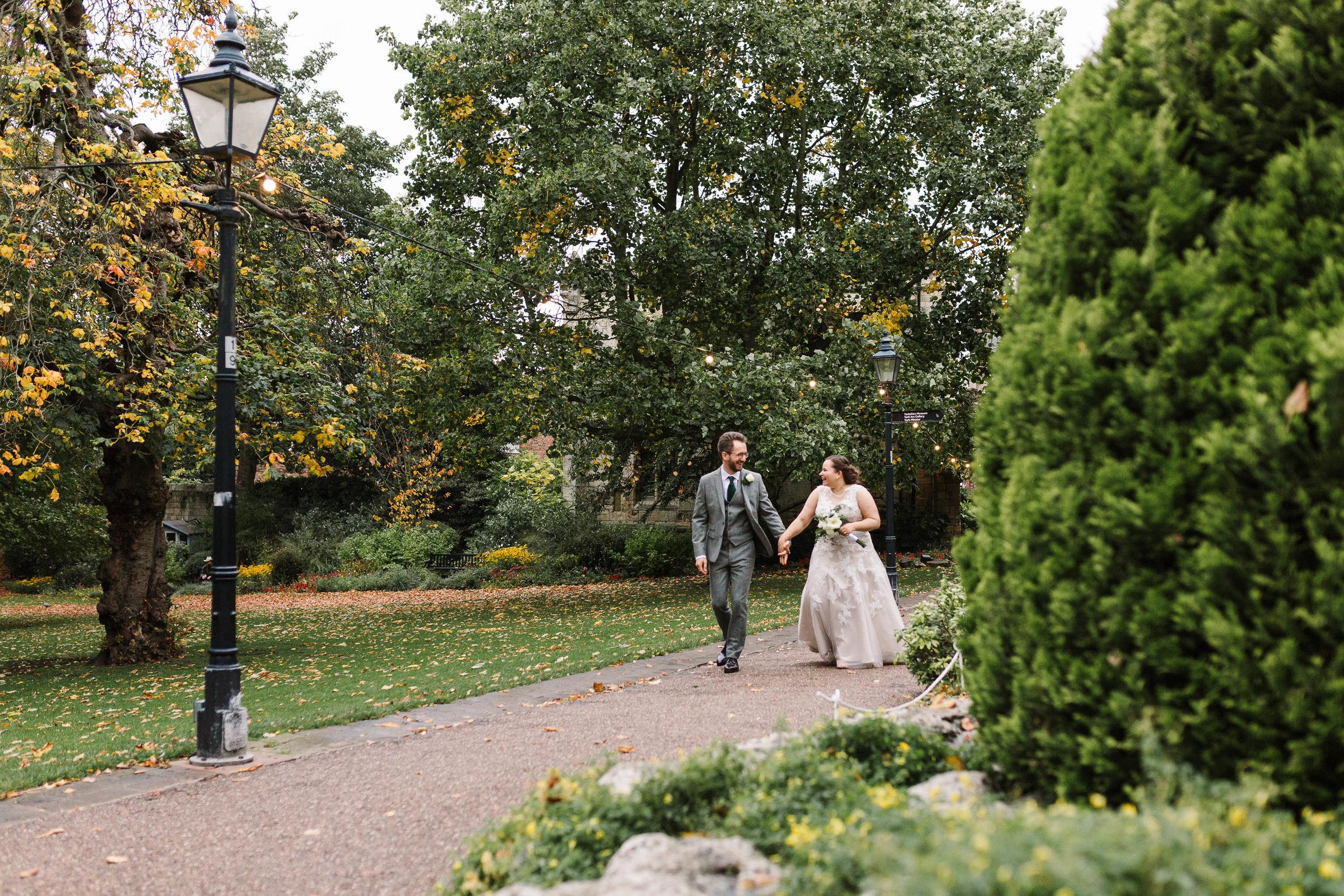 bride and groom walking through museum gardens in york