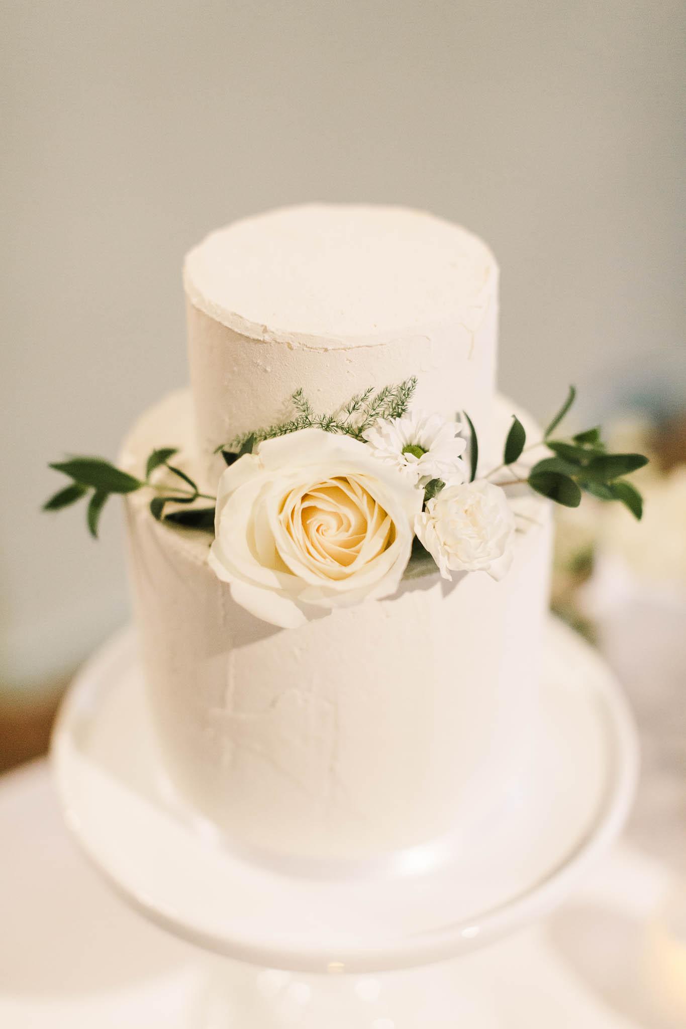 white wedding cake with ivory rose