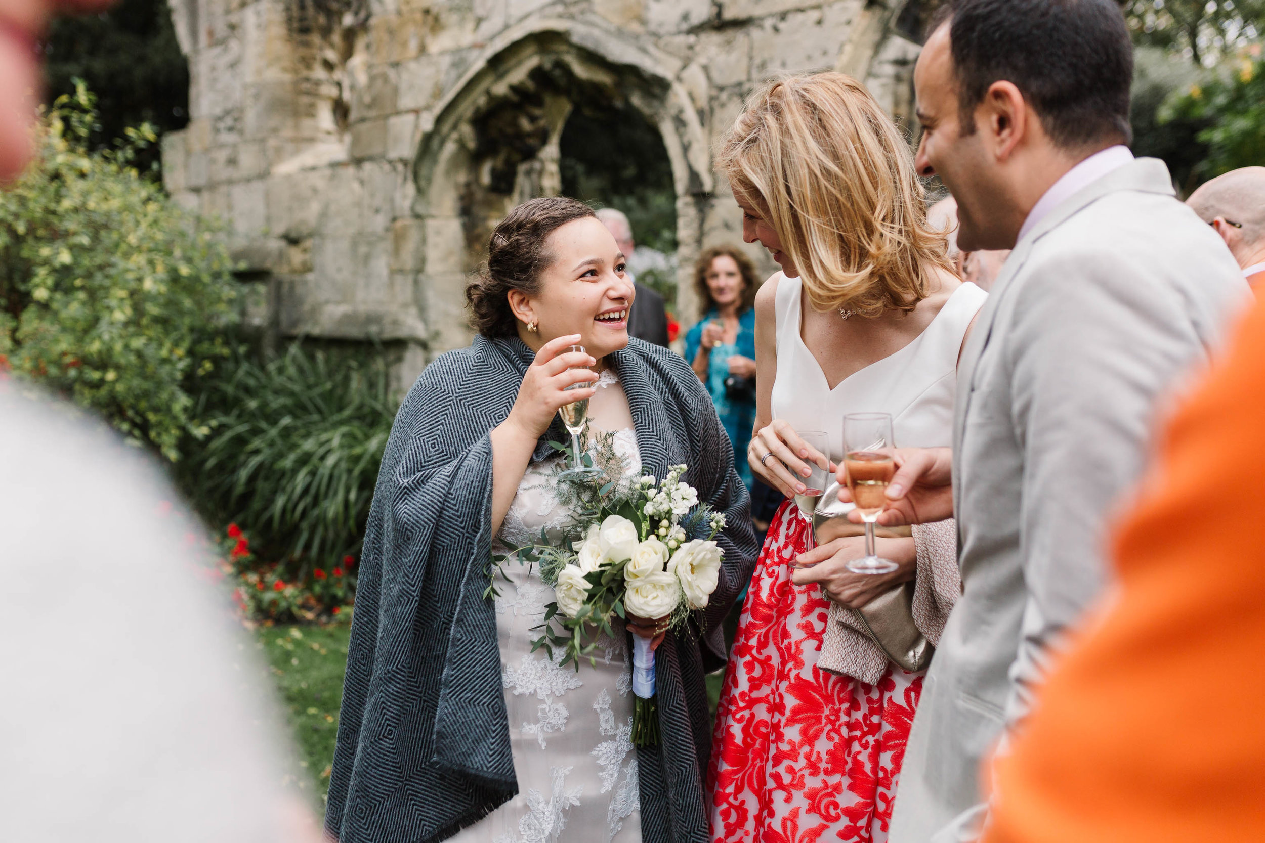bride laughing with guests at autumn wedding