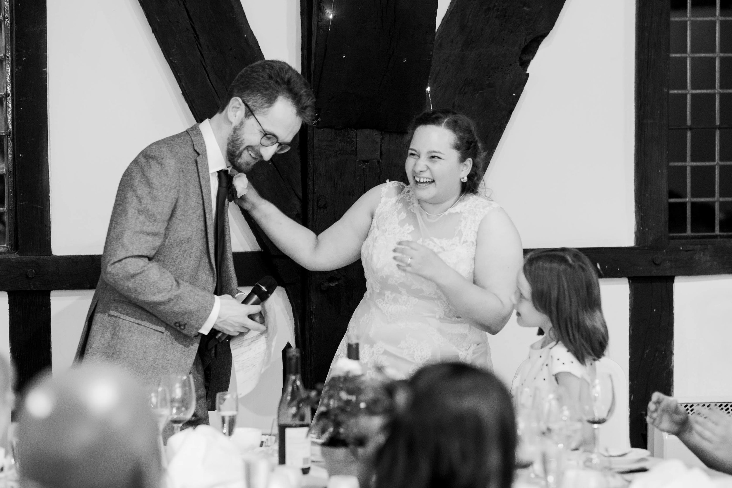bride and groom laughing as they give speech