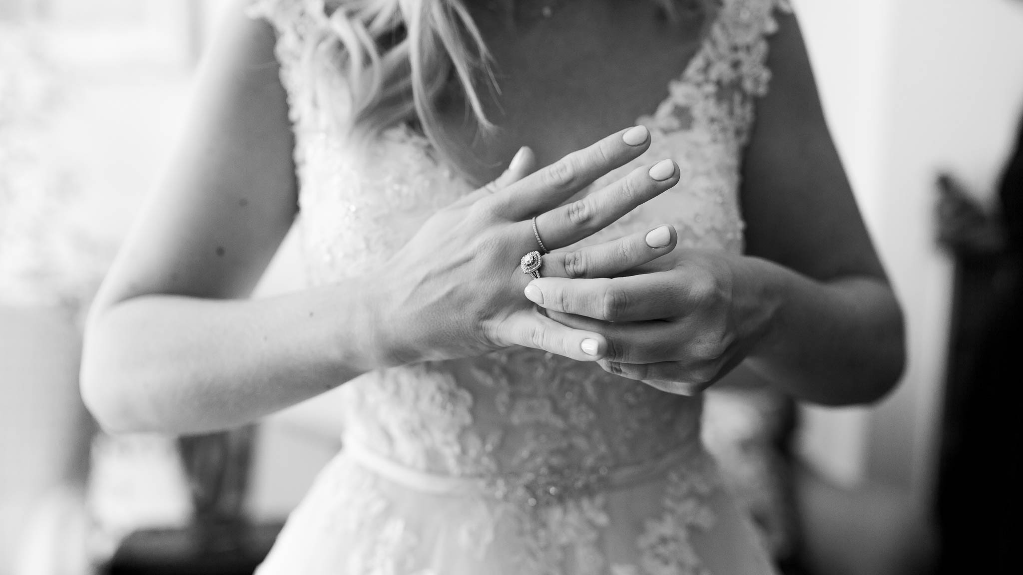 bride putting engagement ring on